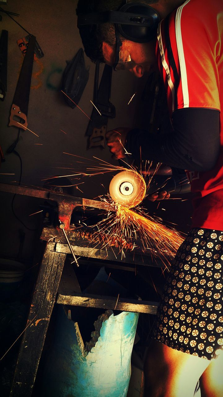 real people, working, occupation, heat - temperature, one person, motion, industry, indoors, holding, skill, metal industry, human body part, standing, work tool, human hand, concentration, expertise, workshop, men, factory, grinding, welder, manual worker, day, people