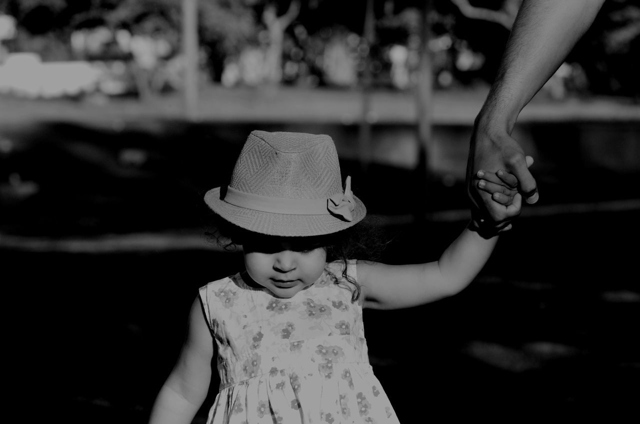 Cropped Hand Of Man Walking With Daughter On Sunny Day
