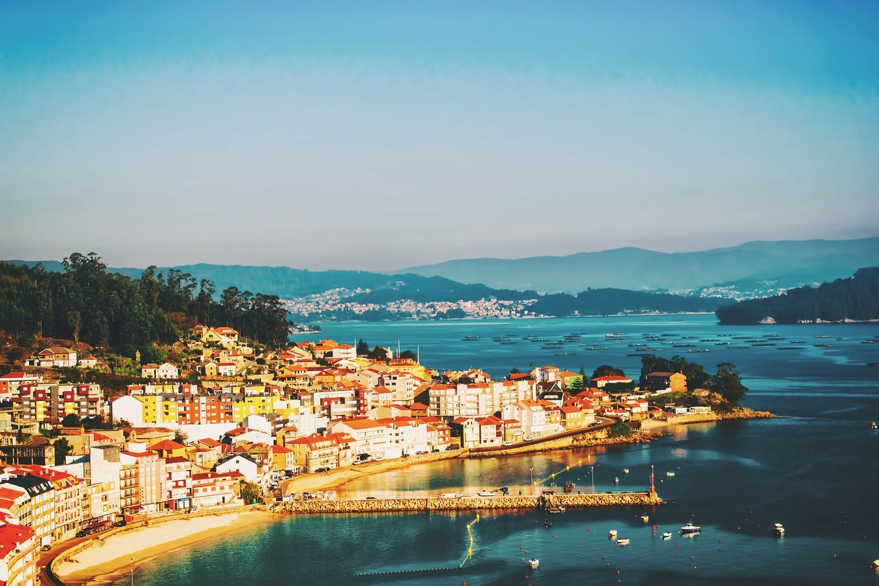 water, mountain, architecture, building exterior, built structure, sea, town, scenics, waterfront, outdoors, beauty in nature, high angle view, sky, nature, no people, city, cityscape, travel destinations, day, illuminated, tree, nautical vessel
