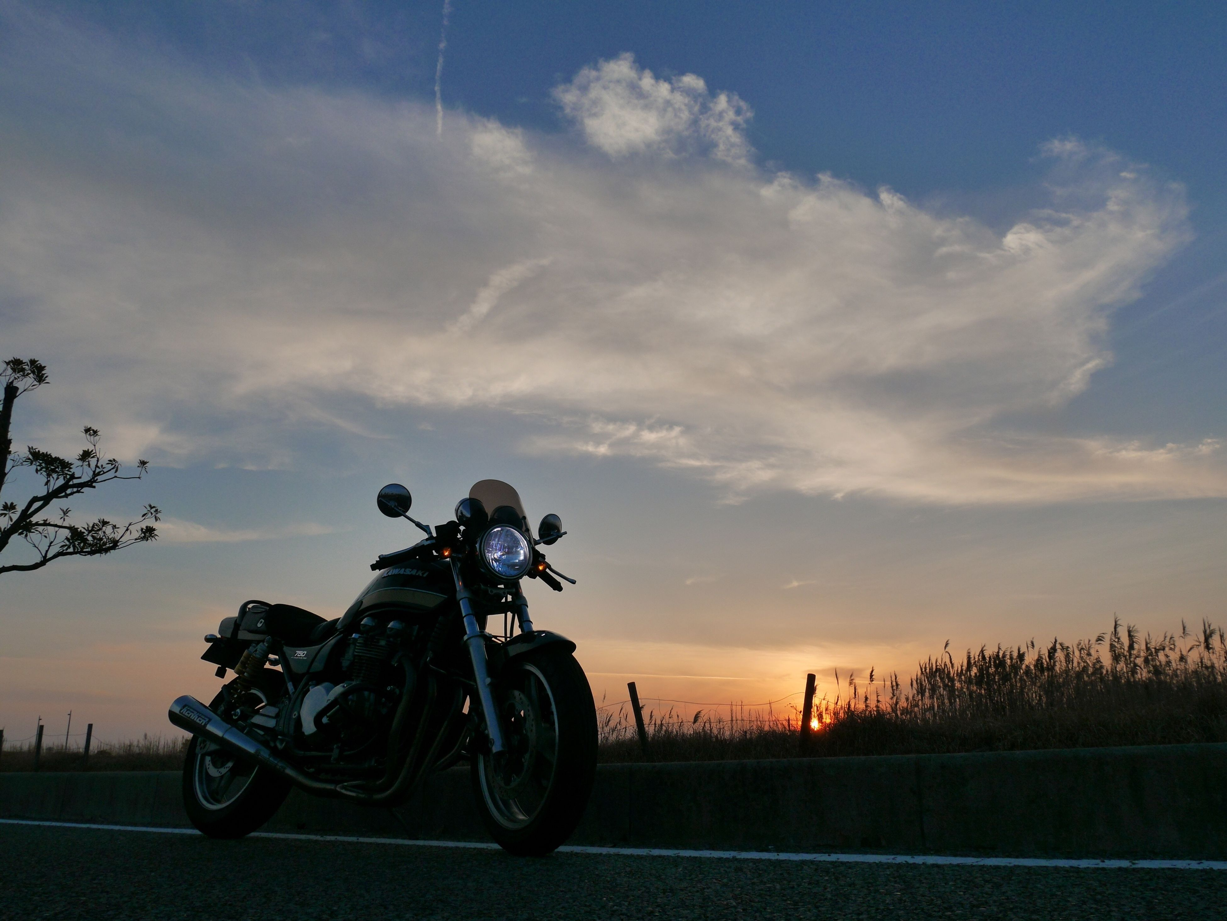 motorcycle, transportation, mode of transport, sky, sunset, cloud - sky, land vehicle, outdoors, adults only, biker, adult, people, only men, one person, headwear, day, motorcycle racing, one man only