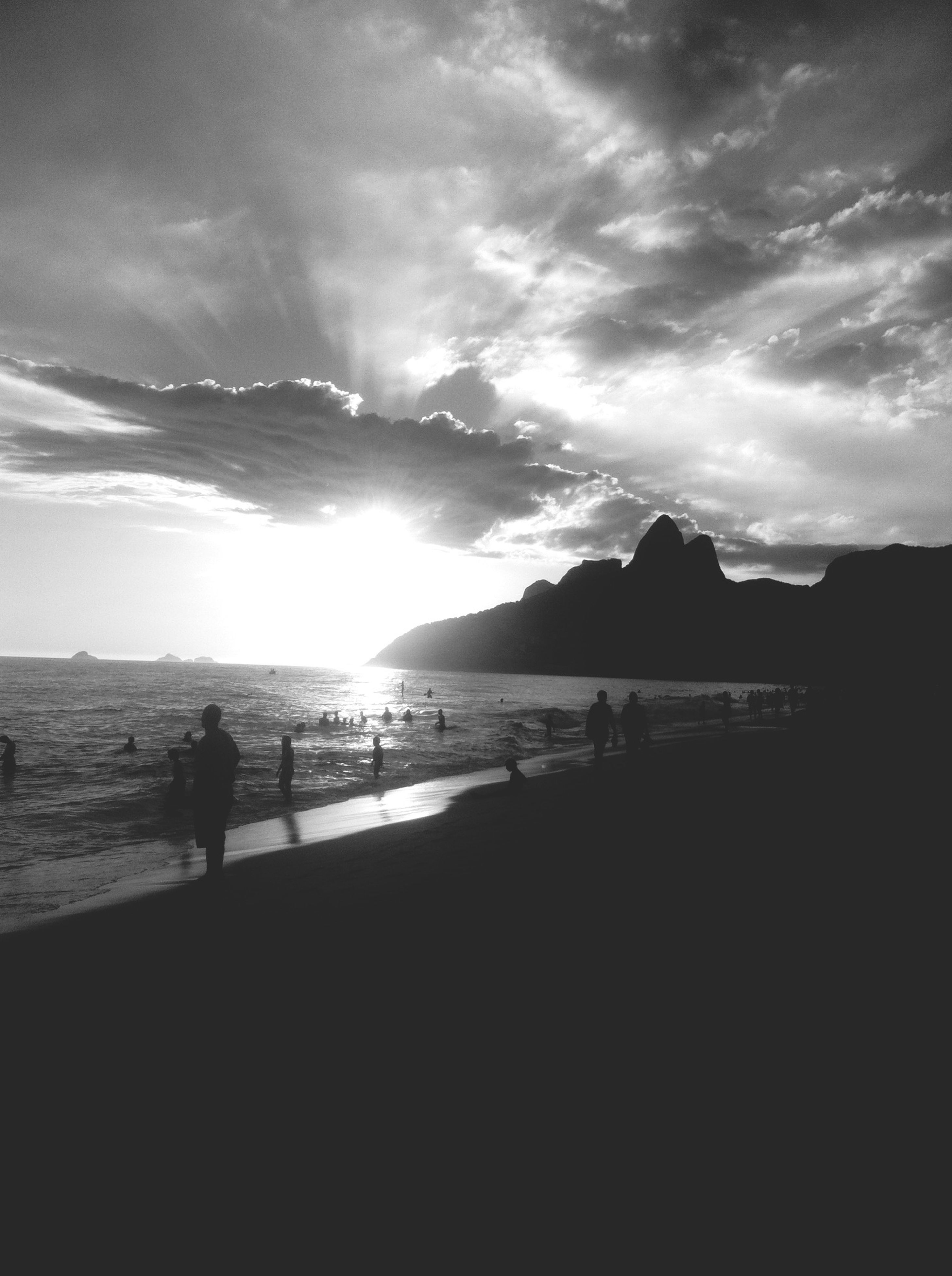 water, sea, silhouette, sky, beach, scenics, tranquil scene, beauty in nature, tranquility, cloud - sky, sunset, leisure activity, shore, lifestyles, nature, men, vacations, mountain, medium group of people