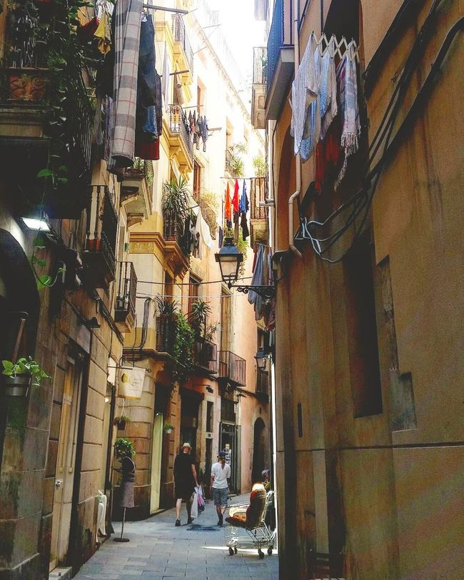 Urban Laundry. Architecture Building Exterior Built Structure Men Street Residential Structure The Way Forward Residential Building City Narrow Building Person Day Alley City Life Outdoors Footpath Barcelona Laundry
