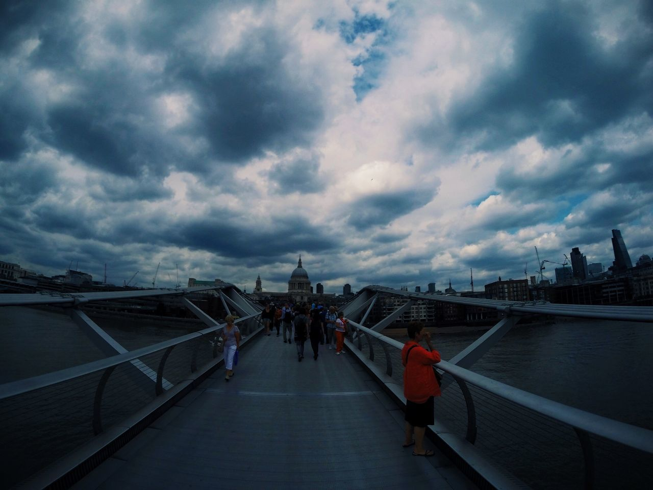 Tourist On Millennium Bridge By St Pauls Cathedral Against Cloudy Sky At Dusk