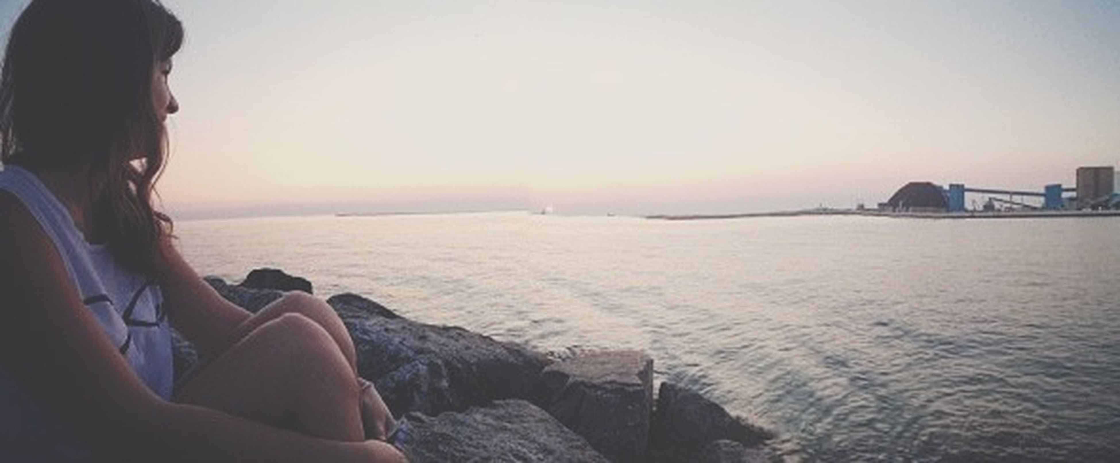 sea, lifestyles, leisure activity, horizon over water, water, beach, clear sky, sunset, sky, person, sitting, holding, vacations, shore, men, scenics, copy space