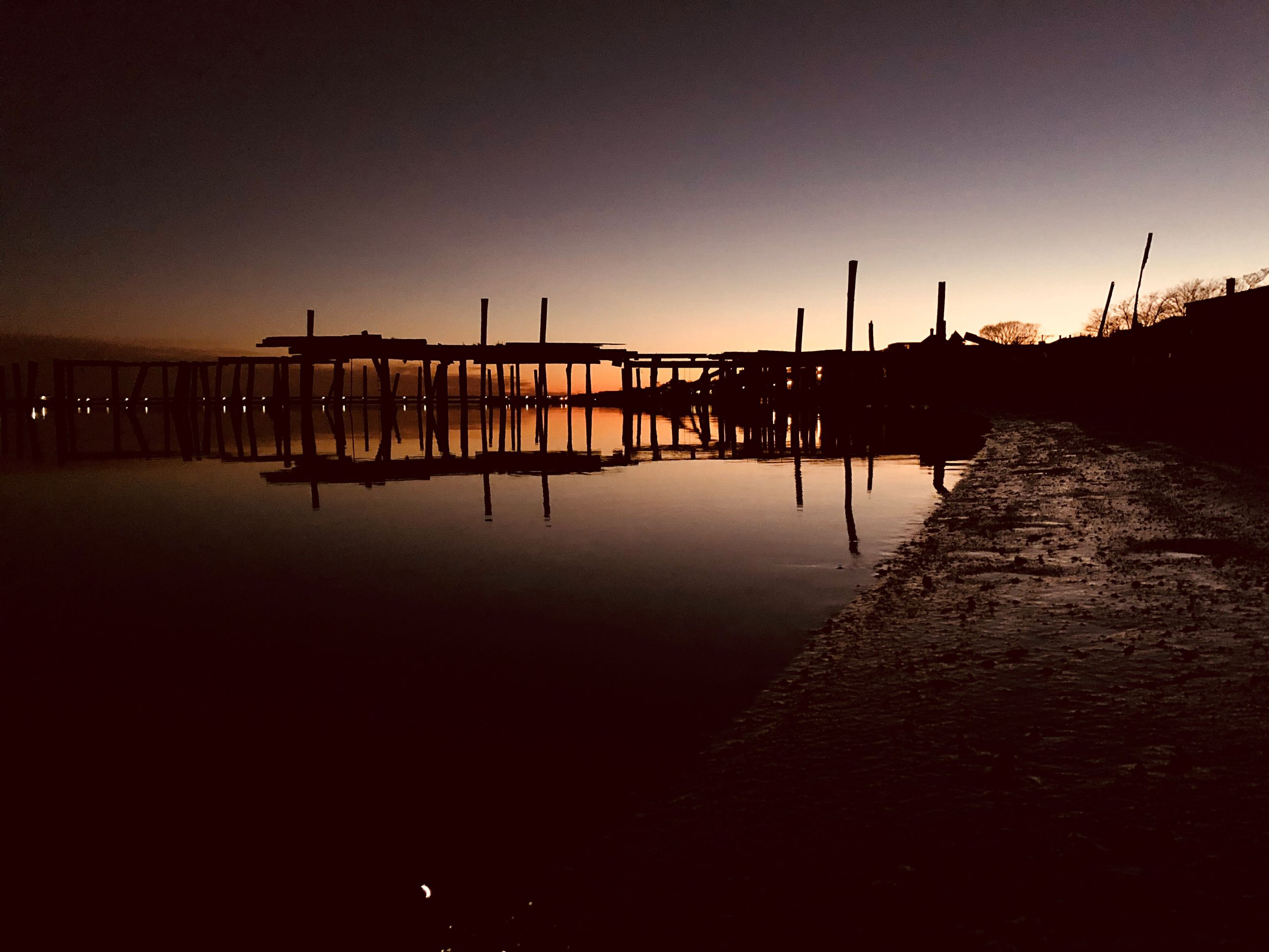sunset, silhouette, water, reflection, sky, outdoors, tranquility, dusk, tranquil scene, built structure, waterfront, no people, river, scenics, clear sky, architecture, nature, beauty in nature, building exterior, city, day