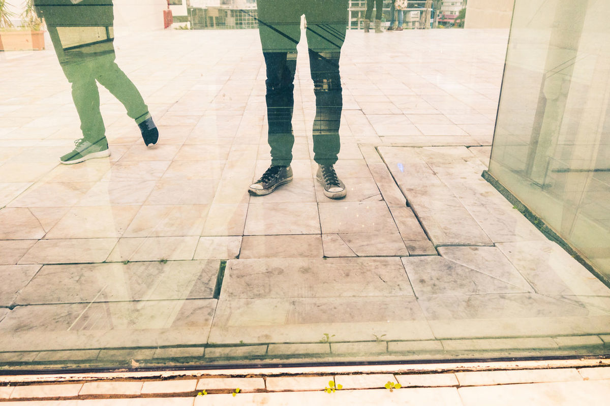 Business City City Life Pants Reflection Concept Conceptual Day Friendship Glass Ground Human Body Part Human Leg Indoors  Lifestyles Low Section Men Men Style People Real People Shoes Standing Togetherness Two Two People