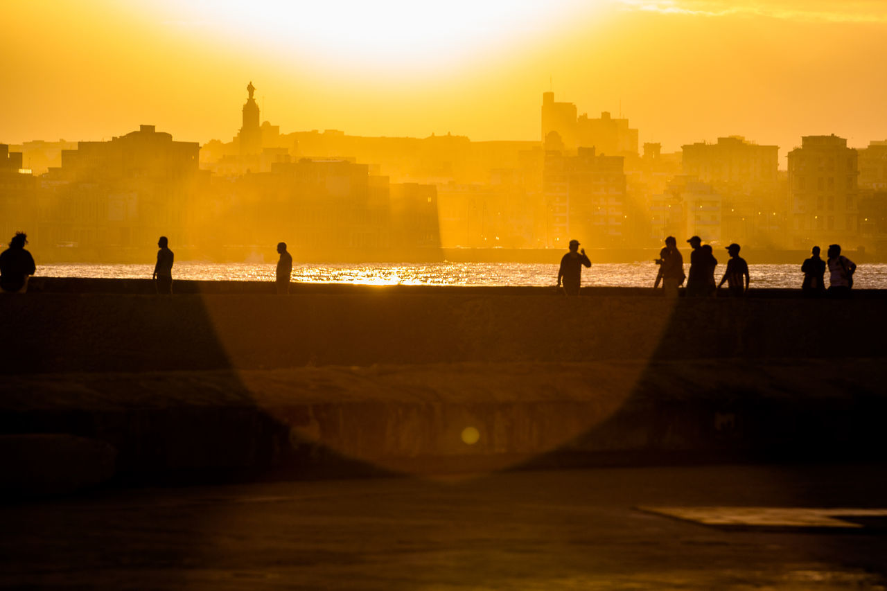 built structure, architecture, building exterior, real people, sunset, leisure activity, silhouette, lifestyles, travel destinations, water, women, men, tourism, large group of people, outdoors, vacations, city, sky, nature, ancient civilization, day, people