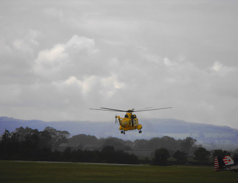 A Yellow Helicopter taking off an airfield Aerospace Industry Air Vehicle Airfield Airshow Blades Cloud - Sky Day Flying Flying Display Foggy Haze Helicopter Hills In The Air Nature No People Outdoors Rescue Sky To The Rescue Transportation Trees Wales Yellow Вертолет