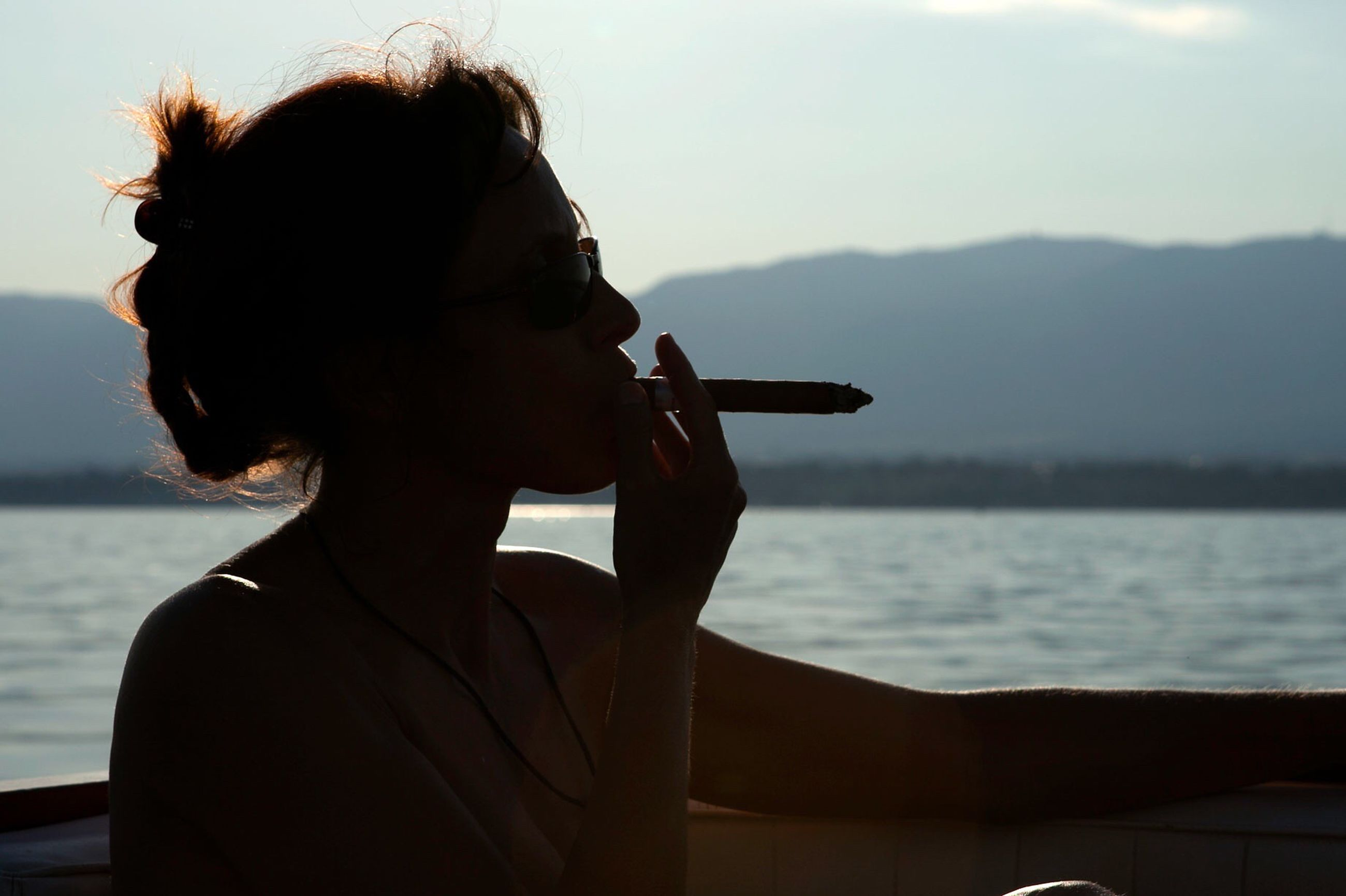 lifestyles, leisure activity, water, sea, focus on foreground, rear view, sky, waist up, headshot, silhouette, sunset, person, three quarter length, photography themes, side view, photographing, nature, holding