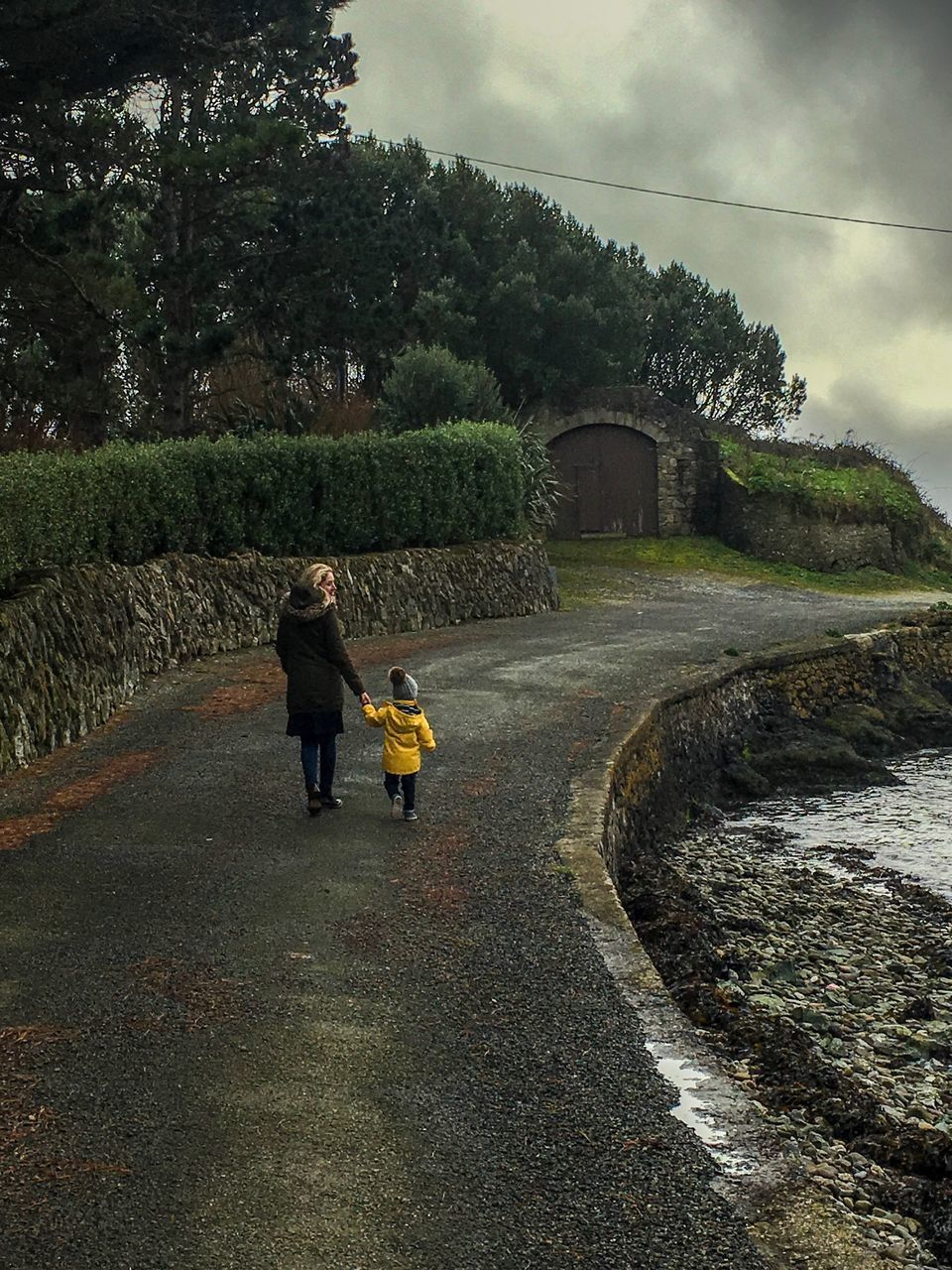 Rear View Of Woman Walking With Daughter On Road Against Cloudy Sky