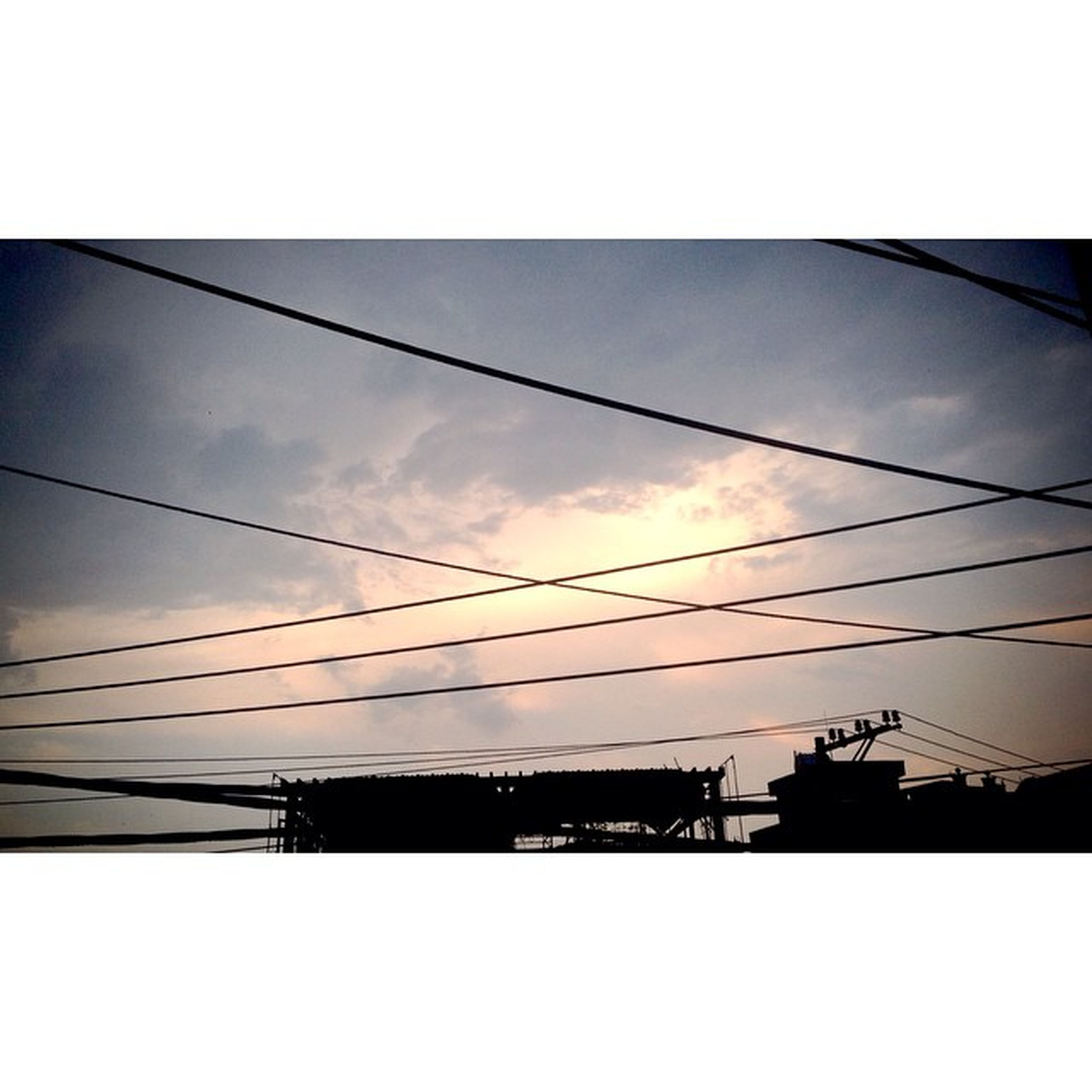 power line, architecture, built structure, low angle view, cable, electricity pylon, building exterior, sky, connection, silhouette, power supply, electricity, power cable, cloud - sky, city, transfer print, auto post production filter, cloud, sunset, dusk