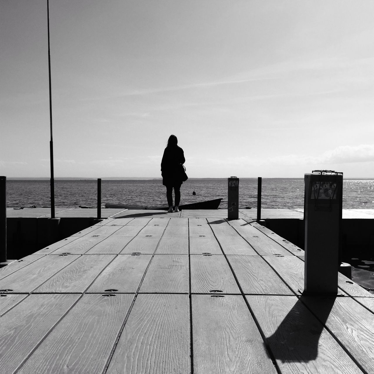 Young Woman Standing On Pier By Sea