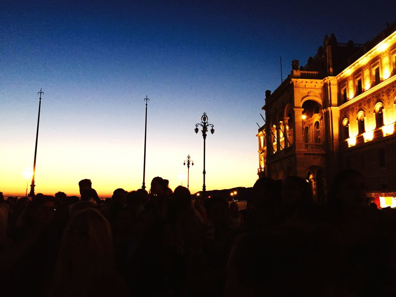 large group of people, architecture, built structure, building exterior, night, illuminated, arts culture and entertainment, real people, silhouette, outdoors, men, togetherness, crowd, sky, sunset, clear sky, people