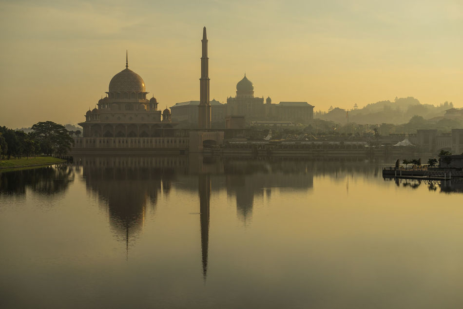 PUTRAJAYA, MALAYSIA - 16TH APRIL 2017; Morning view in Putrajaya, a well planned city, 25 km south of Kuala Lumpur, that serves as the federal administrative centre of Malaysia. Administration Architecture Building Exterior Built Structure City Day Dome History Lake View Morning Light Nature No People Outdoors Place Of Worship Putrajaya, Malaysia Reflection Reflections In The Water Religion Rippled Water Sky Spirituality Sunset Travel Destinations Water Waterfront