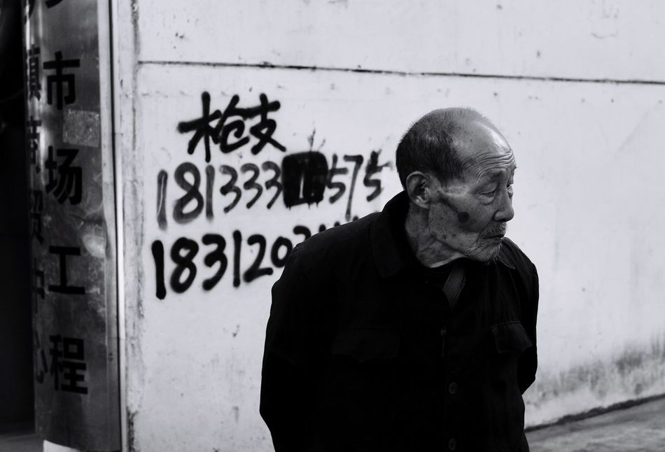 oldman and gun(the number on the wall is illegal advertisement of selling guns) EyeEm Streetphotography Blackandwhite Oldman Capture The Moment China Leicacamera Leicam Gun Social Issues