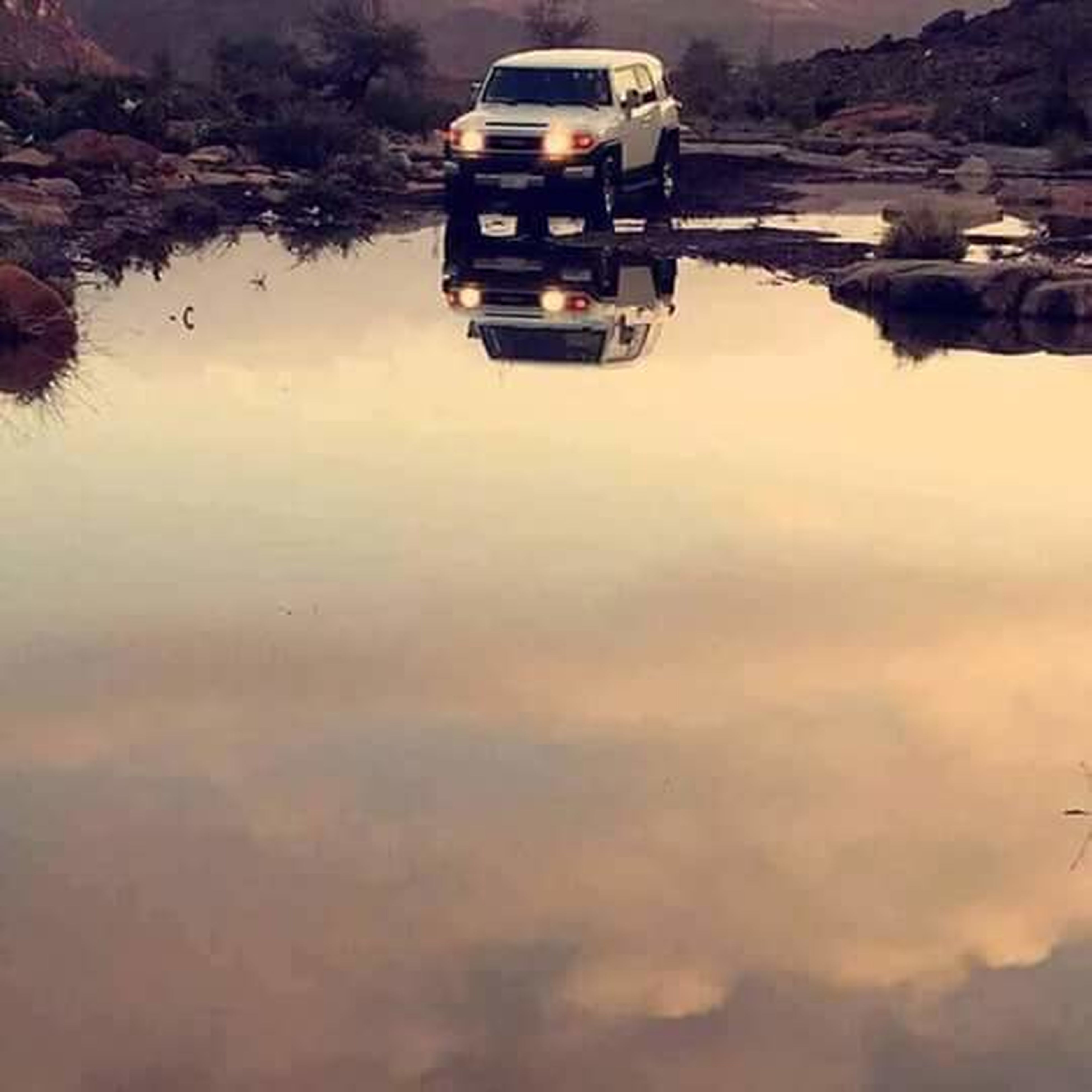 transportation, reflection, mode of transport, water, waterfront, lake, land vehicle, cloud, mountain, tranquility, calm, day, outdoors, sky, nature, beauty in nature, tranquil scene, scenics, water surface, no people