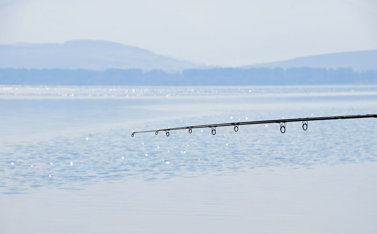 Fishing rod over blue water of lake and horizon with mountain range Blue Day Fishing Fishing Rod Hobby Lake Leisure Leisure Activity Lifestyles Moment Morning Mountain Nature No People Non-urban Scene Relaxing Rod Season  Spinning Time Tranquil Tranquil Scene Tranquility Water Weekend