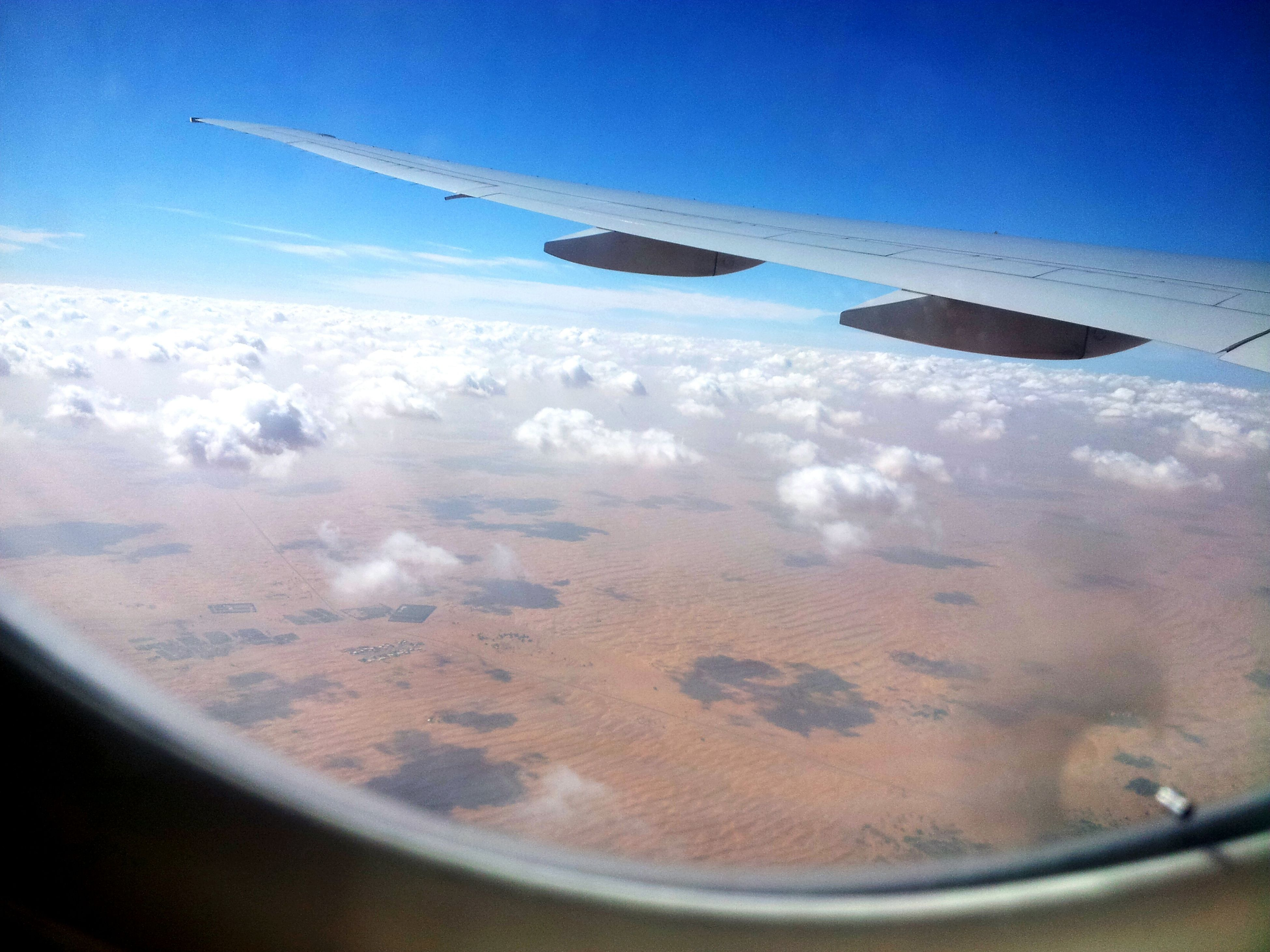 transportation, airplane, air vehicle, mode of transport, aircraft wing, flying, part of, travel, cropped, aerial view, journey, public transportation, mid-air, on the move, vehicle interior, vehicle part, sky, window, airplane wing, aeroplane