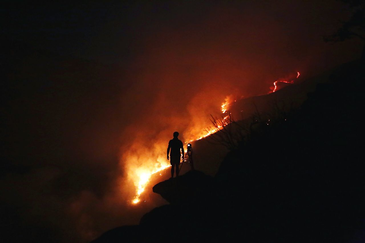 Silhouette Man Standing With Camera Against Forest Fire