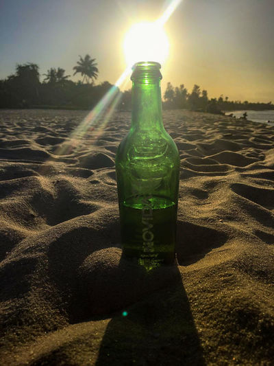 Alcohol Beach Bottle Close-up Day Drink Food And Drink Freshness Green Color Nature No People Outdoors Sand Shadow Sky Sunbeam Sunlight Sunset Water