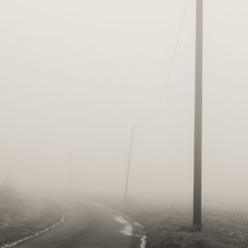 The road disappears into the enveloping mist Bend In The Road Hampshire, UK Misty Morning Madness Monochrome Misty Morning No People Outdoors Southwick Square Format Telegraph Poles In The M Tranquil Scene Weather