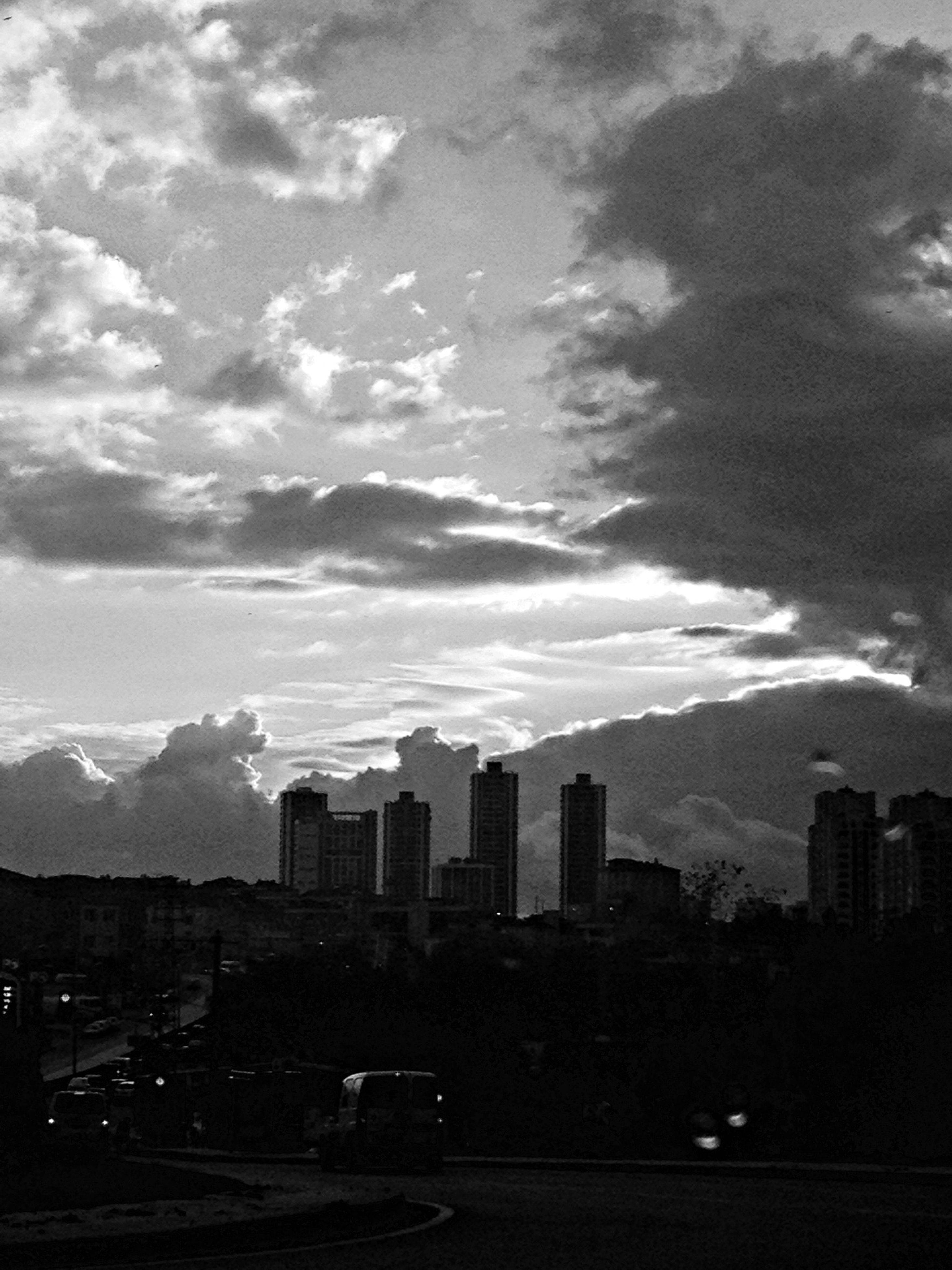 building exterior, architecture, built structure, city, sky, cloud - sky, skyscraper, cityscape, cloudy, office building, modern, tall - high, city life, building, cloud, tower, urban skyline, car, dusk, transportation