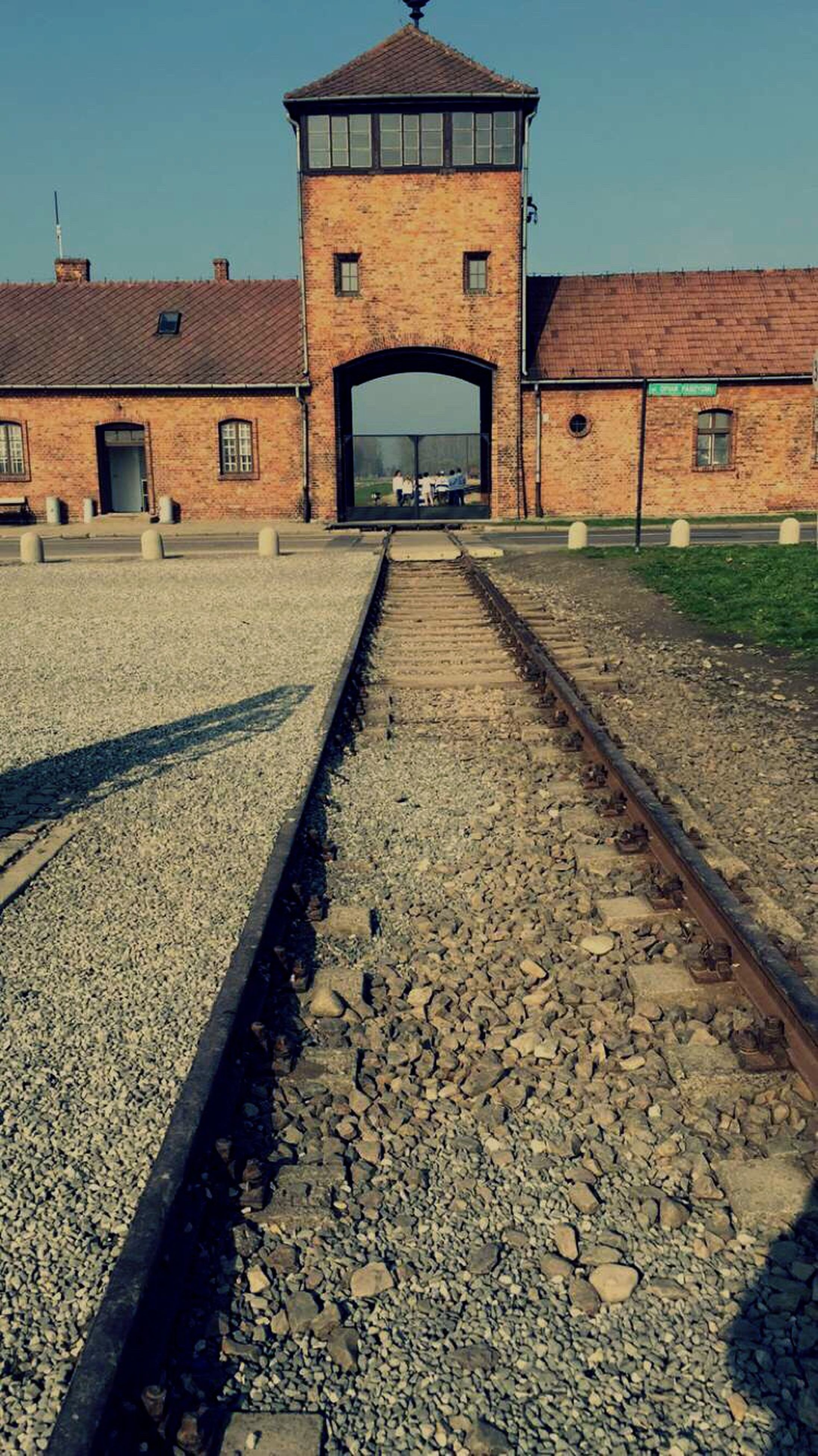 architecture, built structure, building exterior, the way forward, diminishing perspective, clear sky, transportation, vanishing point, cobblestone, house, residential structure, street, surface level, residential building, sky, day, railroad track, building, city, outdoors