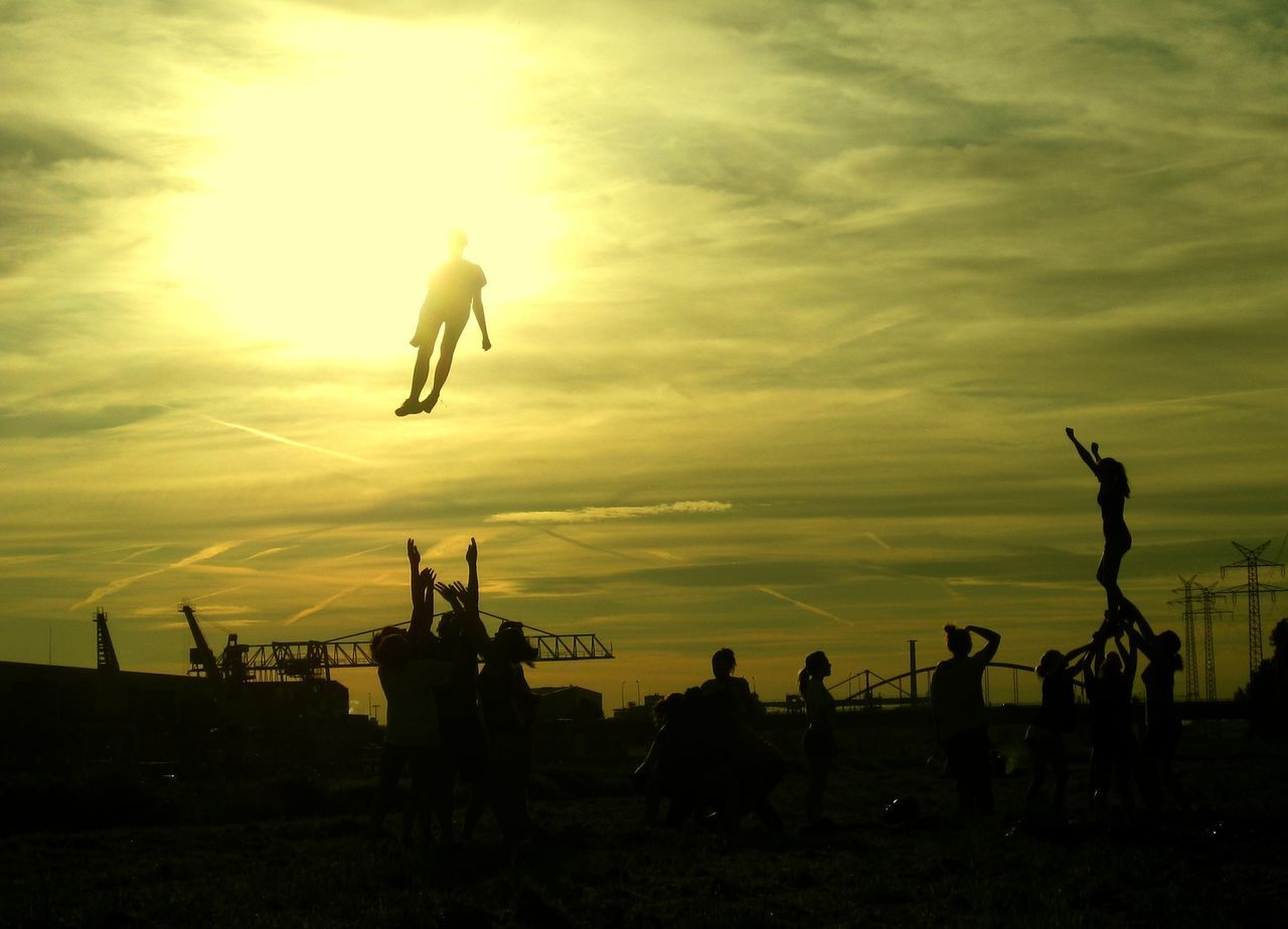 Sunset Silhouettes Flying Jumping Leisure Activity Outdoors Real People Silhouette Sky Strong Together Sunset Teamspirit Togetherness Victory