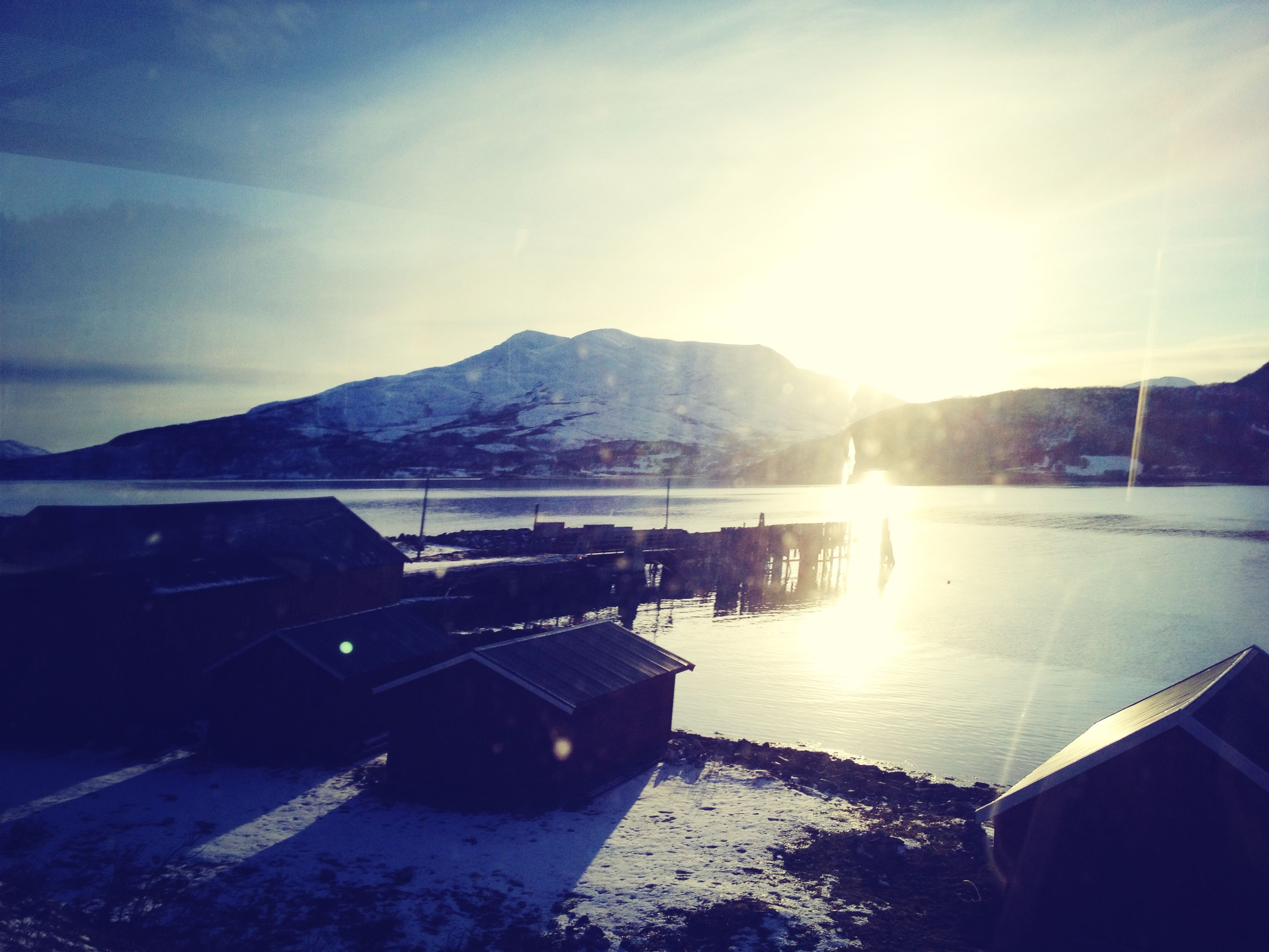 mountain, mountain range, snow, winter, cold temperature, sky, sun, scenics, tranquil scene, beauty in nature, water, tranquility, sunbeam, sunlight, nature, lake, cloud - sky, weather, season, lens flare