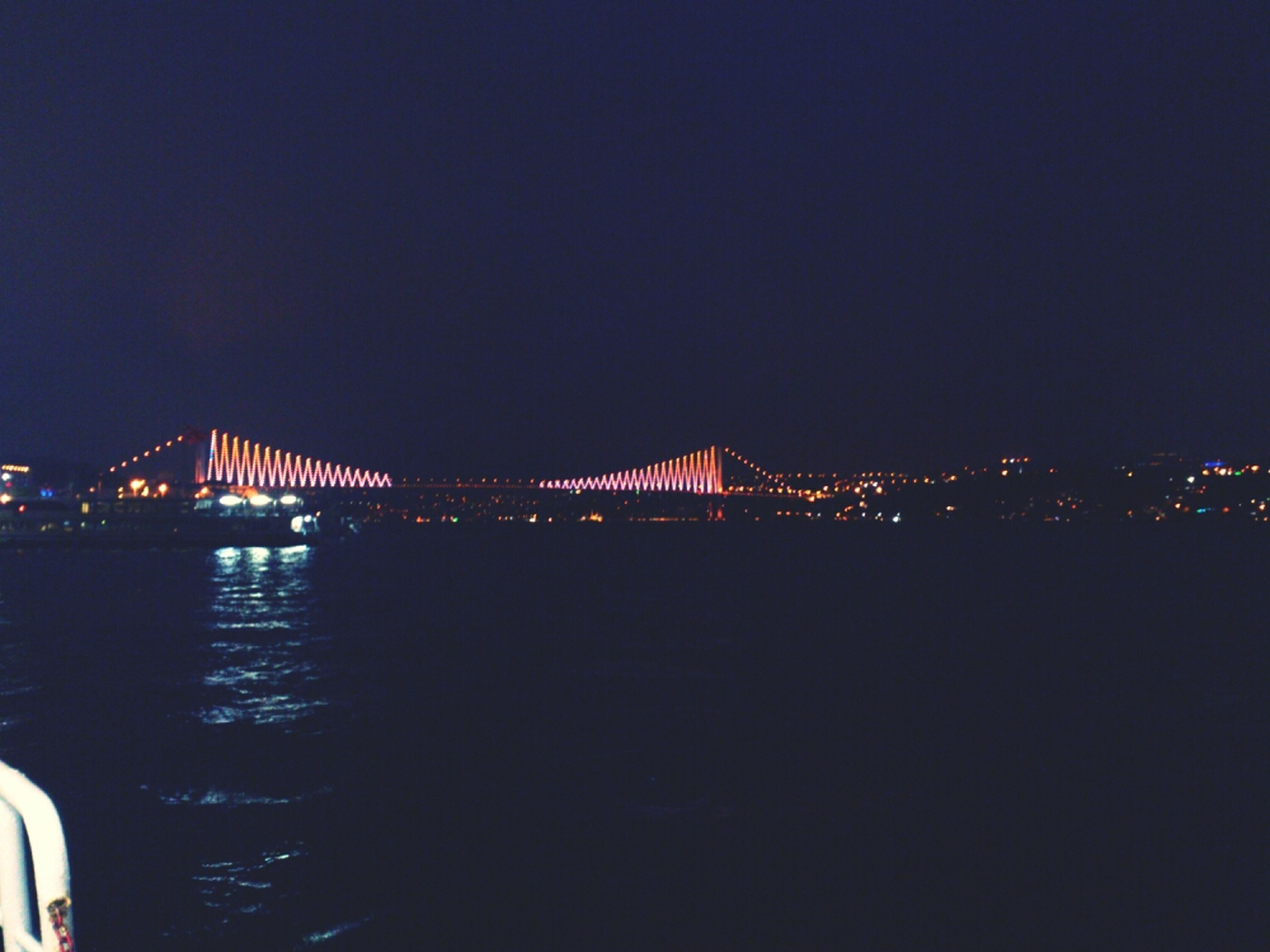illuminated, night, water, architecture, built structure, bridge - man made structure, copy space, connection, clear sky, river, bridge, reflection, waterfront, city, engineering, dark, building exterior, suspension bridge, sky, travel destinations