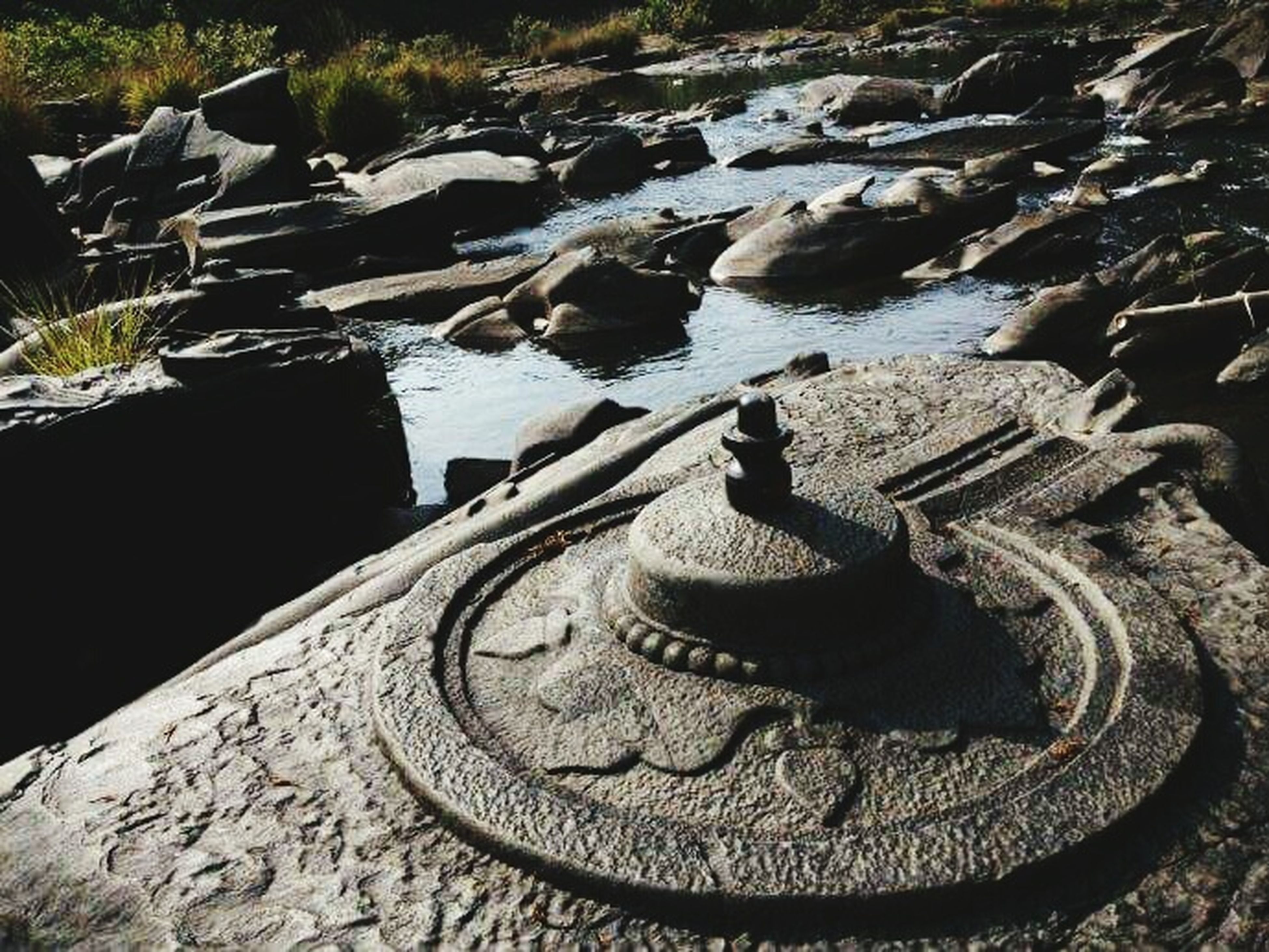 high angle view, rock - object, day, art and craft, outdoors, stone material, sunlight, sculpture, no people, art, nature, built structure, old, history, close-up, statue, creativity, water, stone - object, stone