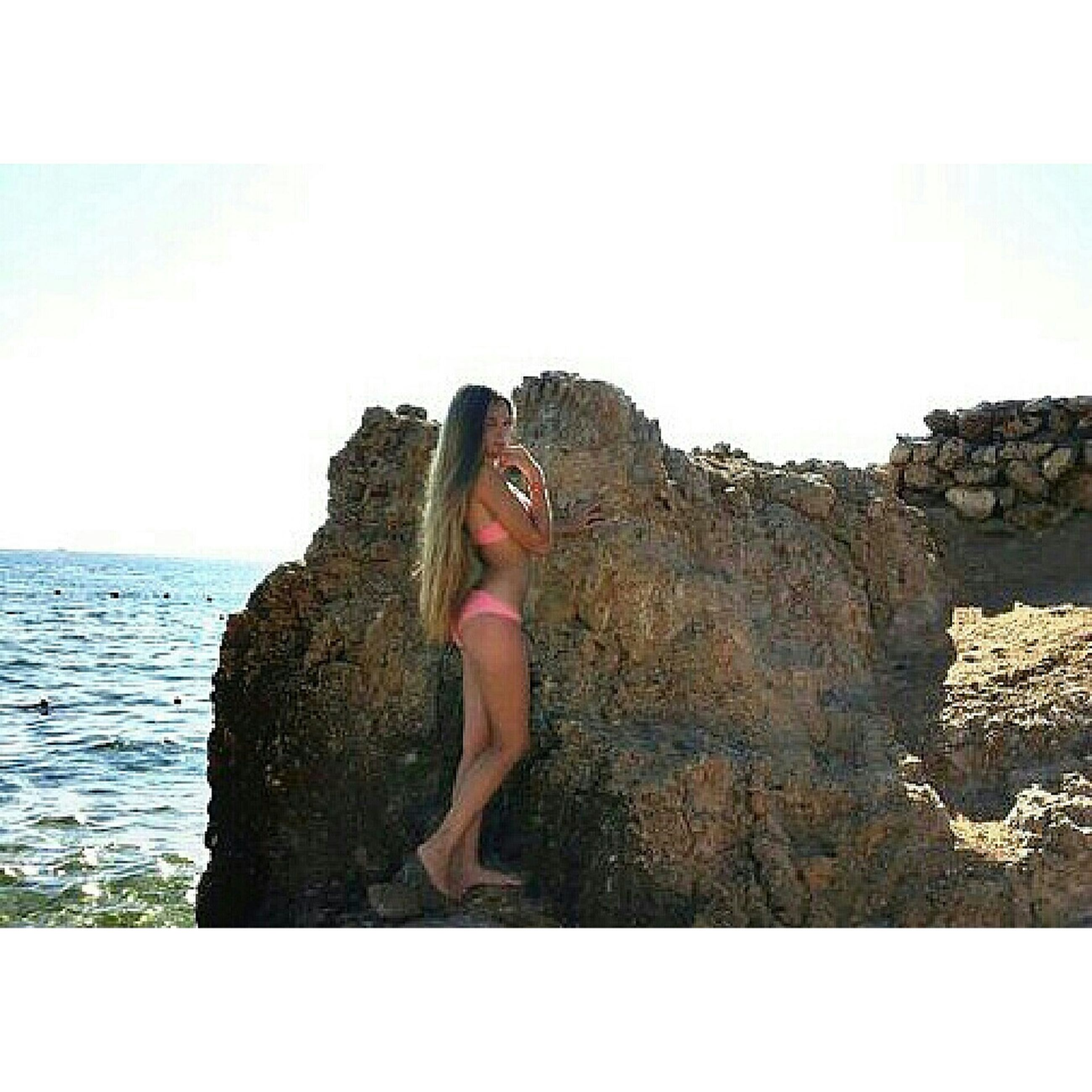 water, sea, lifestyles, leisure activity, rock - object, horizon over water, tranquility, scenics, beauty in nature, nature, tranquil scene, person, vacations, rock formation, young adult, standing, rock, sitting