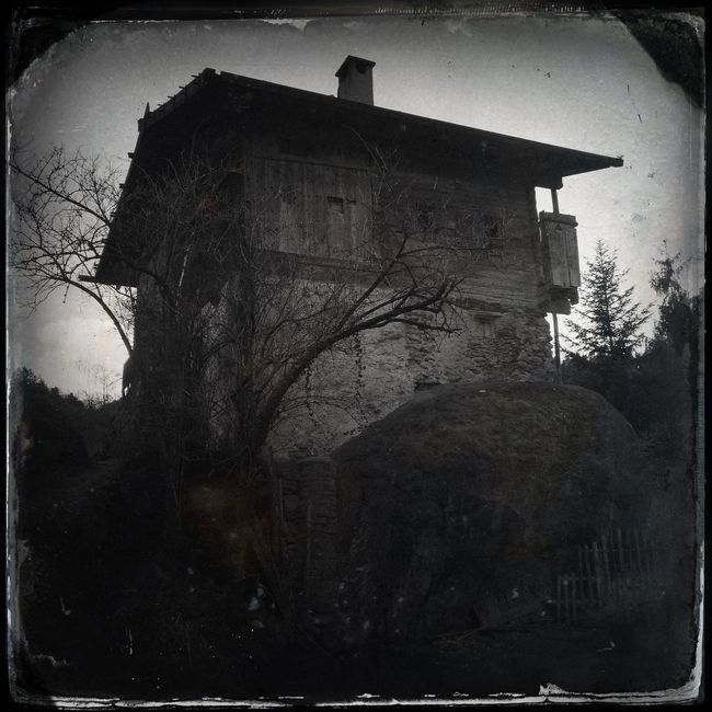 """Originally standing on a meadow, the """"Häusl am Stoan"""" (house on the stone) survived the flood of 1882 only because it had been built on a huge block of stone. The entire surrounding ground was swept away Blackandwhite Hipstamatic The_guido"""