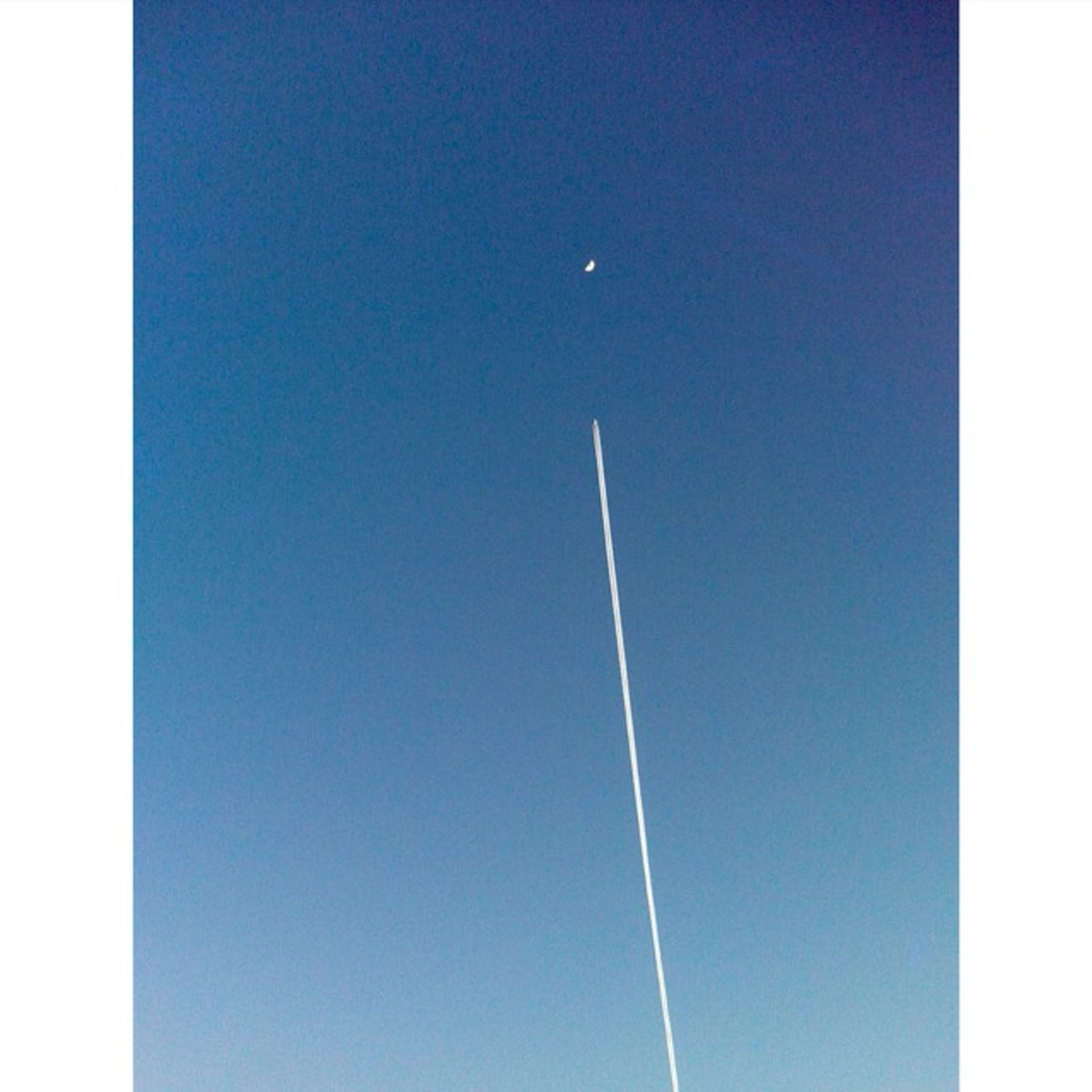 blue, clear sky, copy space, low angle view, transfer print, auto post production filter, vapor trail, high section, street light, no people, outdoors, nature, day, sky, lighting equipment, flying, beauty in nature, pole, moon, tranquility