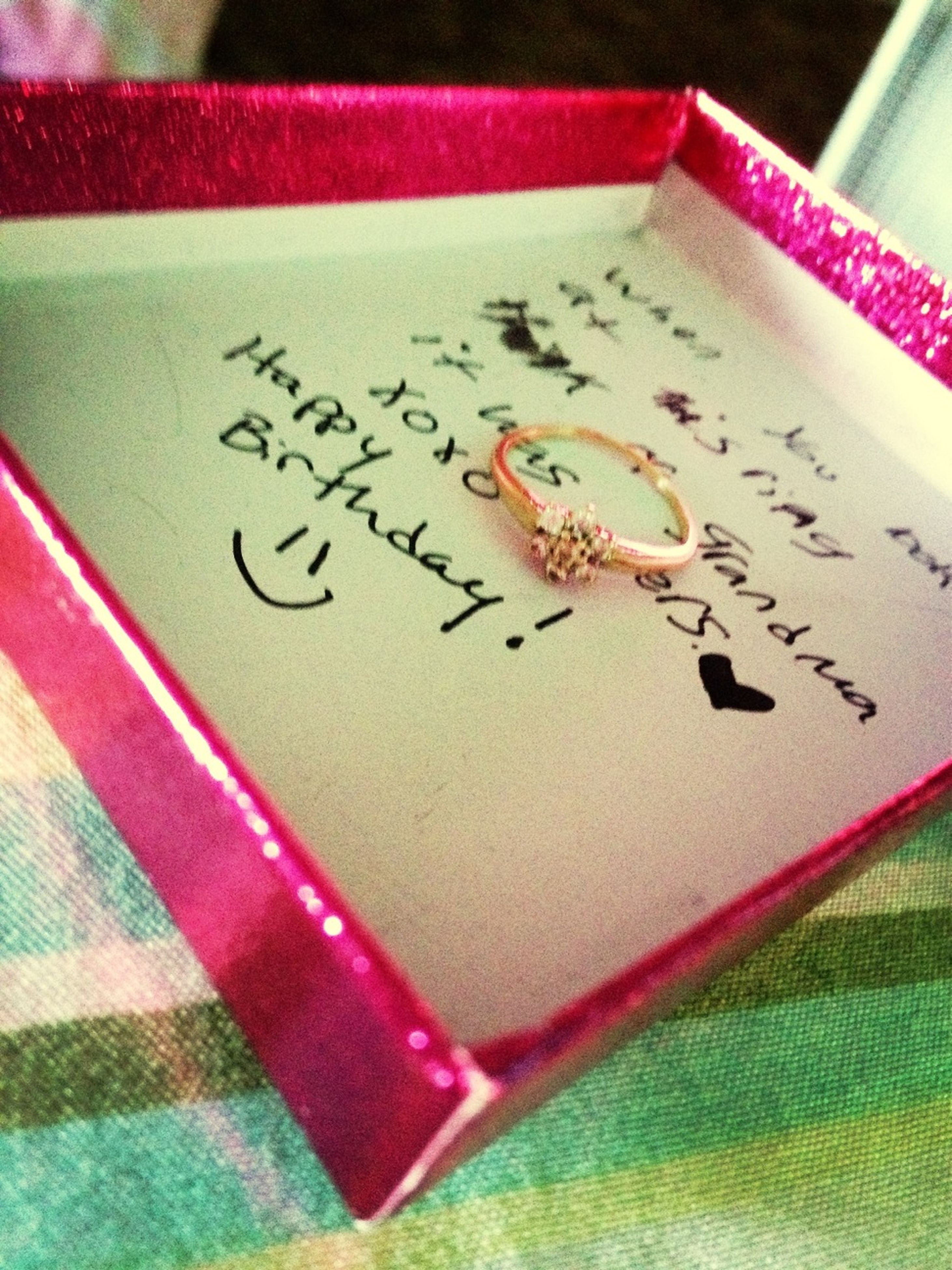 indoors, text, still life, table, communication, western script, paper, close-up, book, education, high angle view, handwriting, art and craft, no people, selective focus, page, creativity, art, pink color, pencil