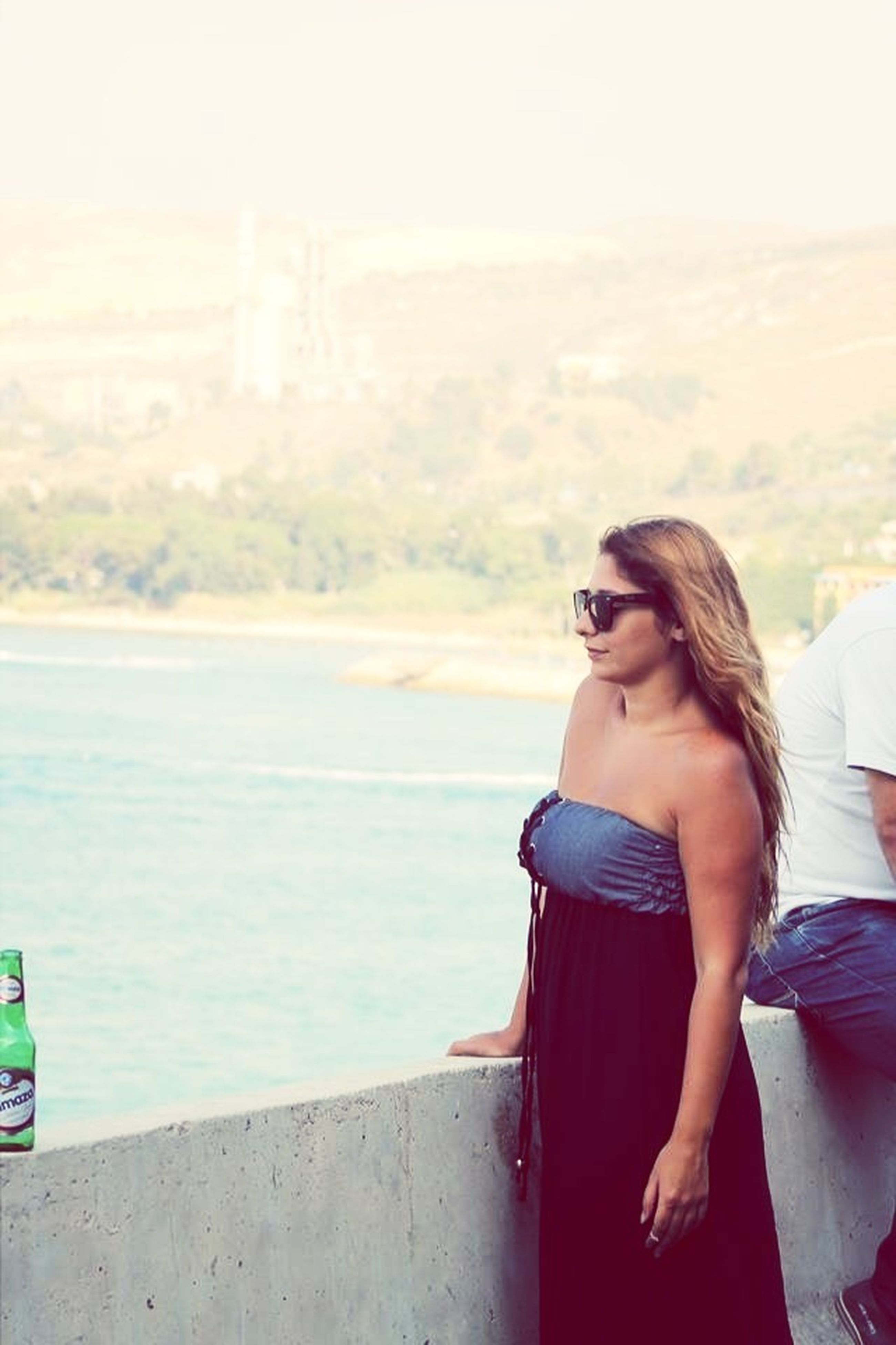 young adult, lifestyles, leisure activity, person, casual clothing, young women, sea, water, beach, sunglasses, focus on foreground, standing, waist up, long hair, side view, sitting, looking at camera, portrait