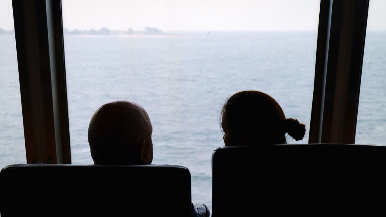 sitting, two people, window, men, sea, water, indoors, rear view, day, togetherness, headshot, women, real people, technology, nature, friendship, people