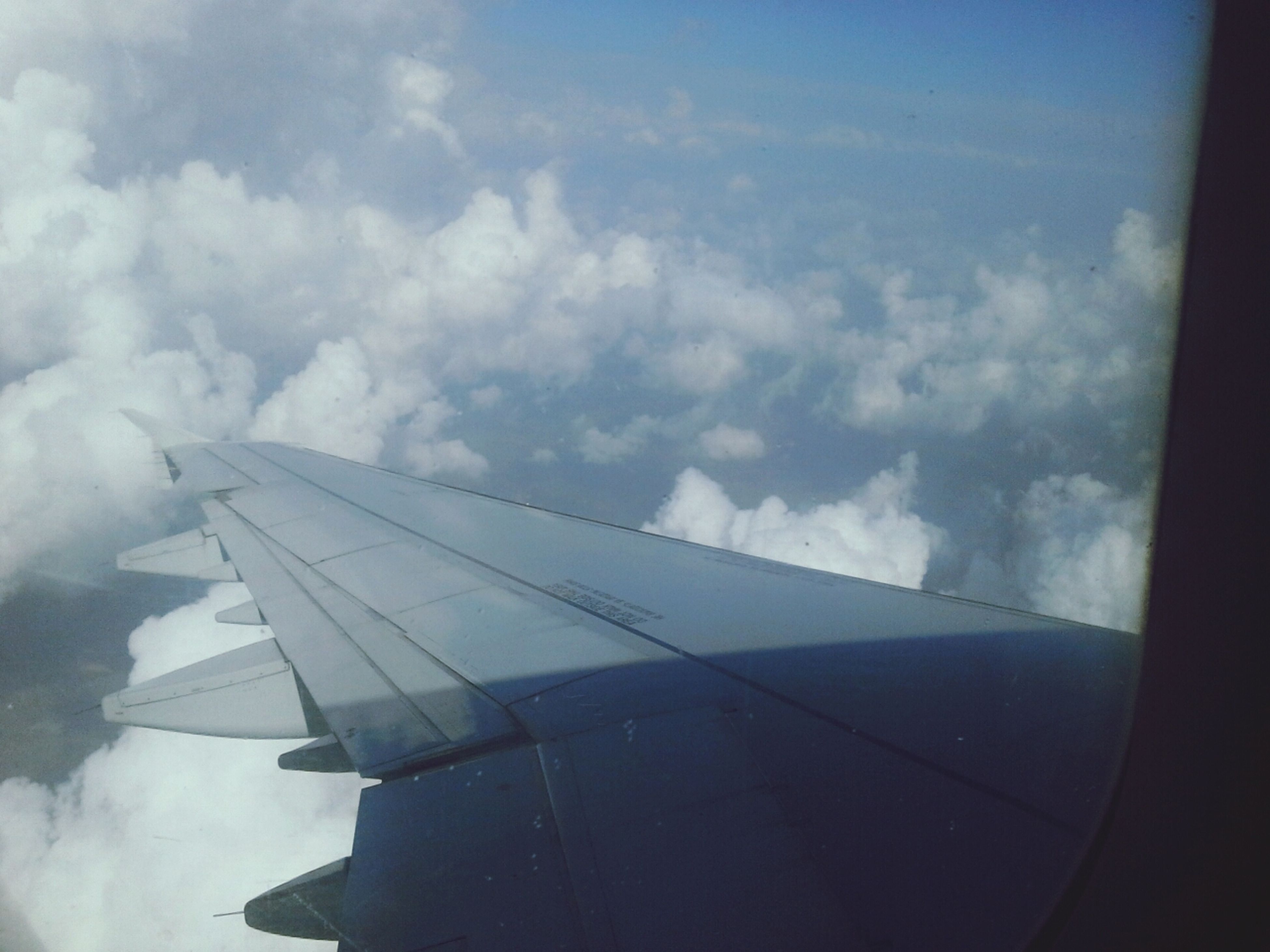 airplane, air vehicle, aircraft wing, sky, transportation, mode of transport, flying, cloud - sky, part of, cropped, cloud, travel, cloudy, built structure, aerial view, architecture, mid-air, journey, day, building exterior