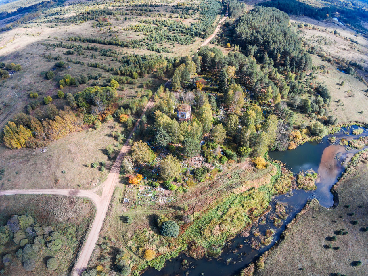 """Aerial view of an abandoned church and cemetery near the river Volchina. From the series """"Flying in the hamlet Lunacharsky."""" A Bird's Eye View Abandoned Abandoned Church Aerial View Beauty In Nature Day Drone  Farm Green Color Growth High Angle View Nature No People Outdoors River Road Rural Top Perspective Tranquility Tree"""