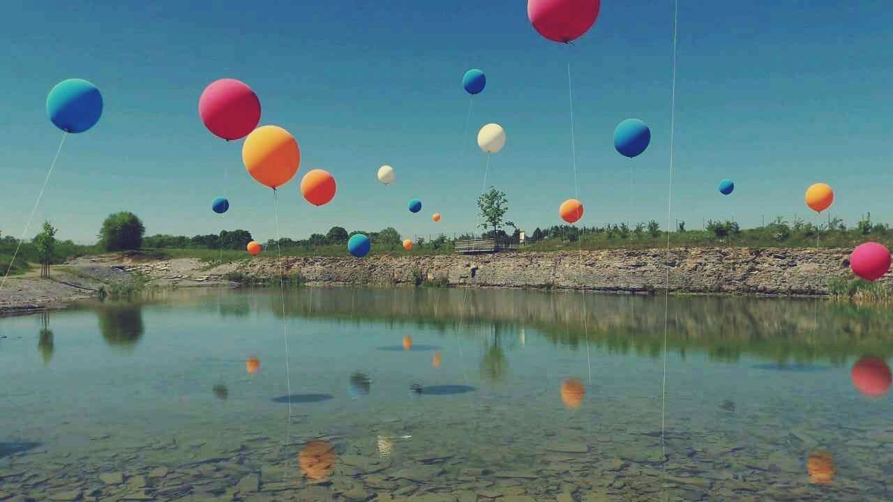 balloon, helium balloon, celebration, multi colored, mid-air, reflection, flying, outdoors, ballooning festival, water, hot air balloon, day, blue, nature, no people, sky