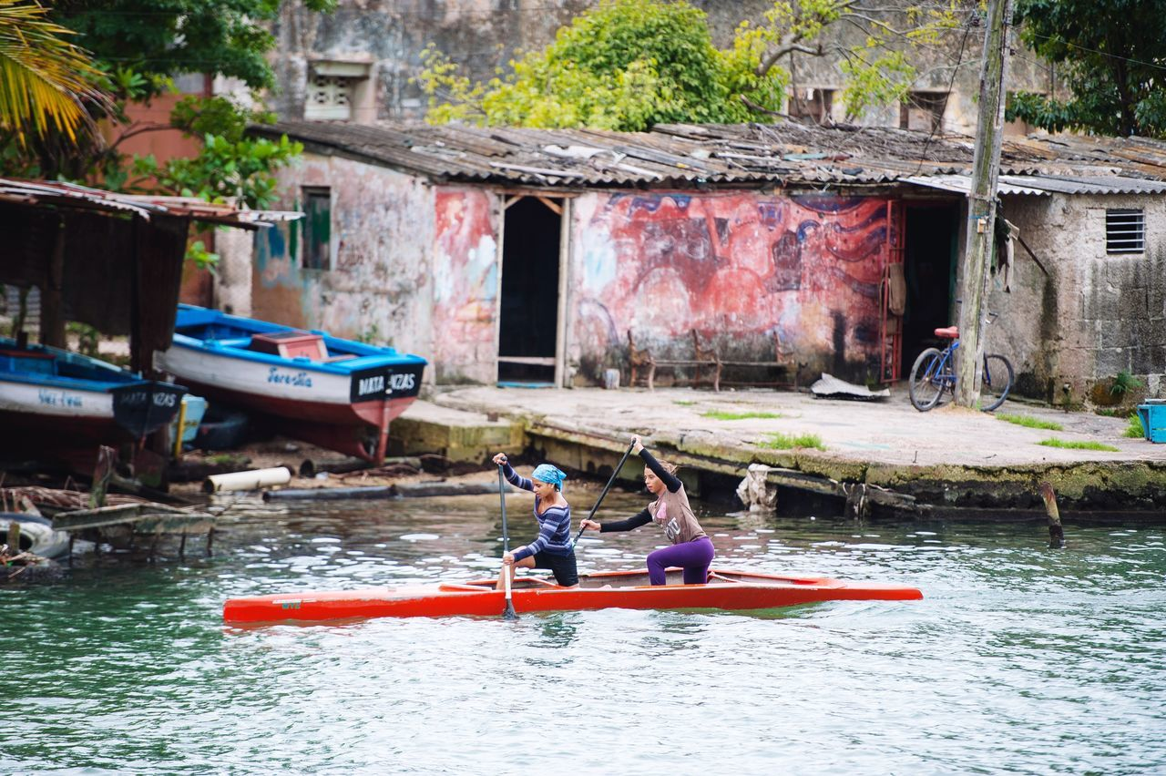 nautical vessel, real people, water, transportation, boat, leisure activity, mode of transport, outdoors, day, oar, river, architecture, men, nature, built structure, building exterior, two people, lifestyles, tree, people