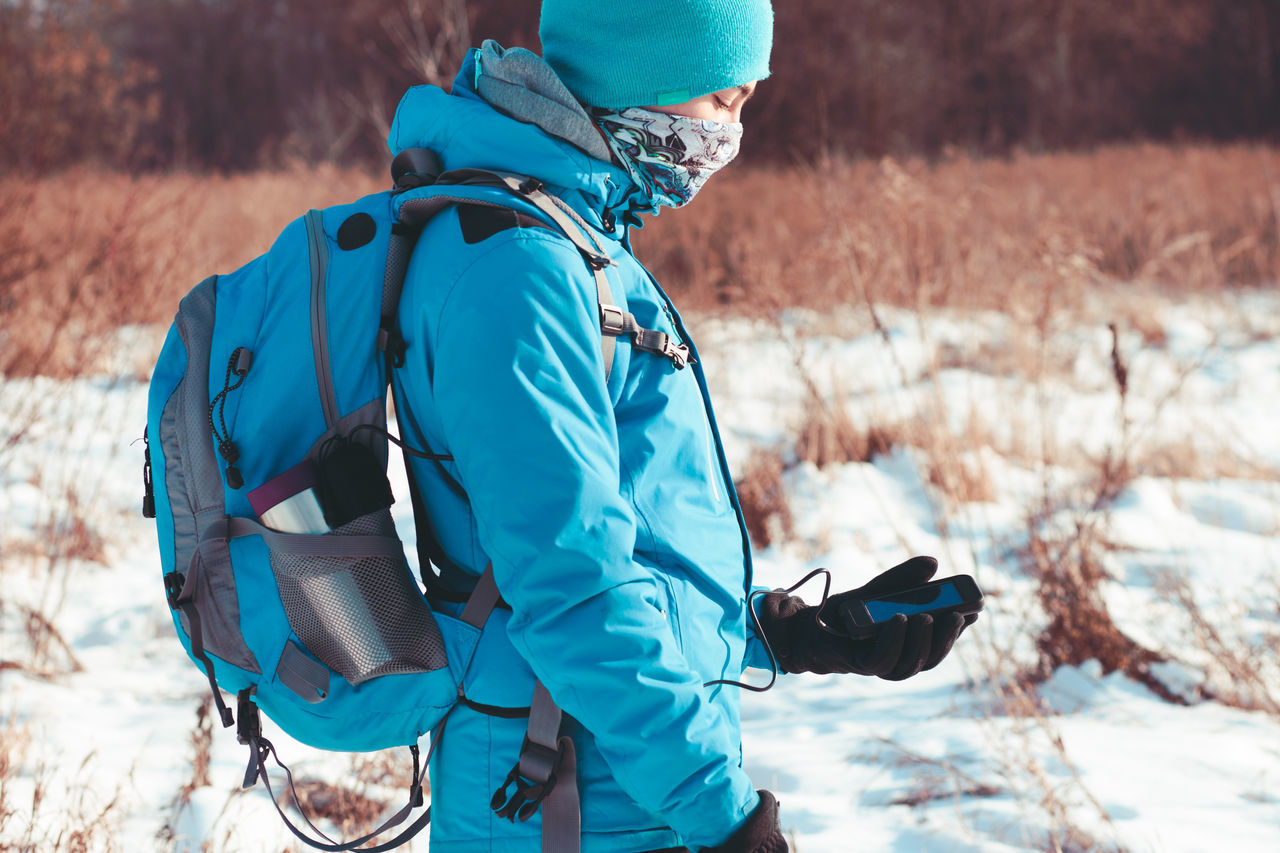 Boy using the mobile phone during the winter trip Active Activity Backpack Bandana Boy Charger Cold Day Hike Hiker Journey Lifestyles Mobile Nature Navigation Outdoors People Person Phone Smart Phone Snow Trip Winter Wintertime
