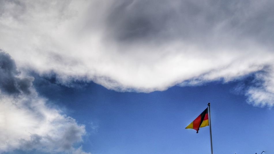 german flag in the blue sky with white clouds Nature Fine Art Eyem Gallery Sky And Clouds Sky Cloudy Flag Flags In The Wind  EyeEm Gallery White Clouds German Flag Black Red Gold Fine Art Photography