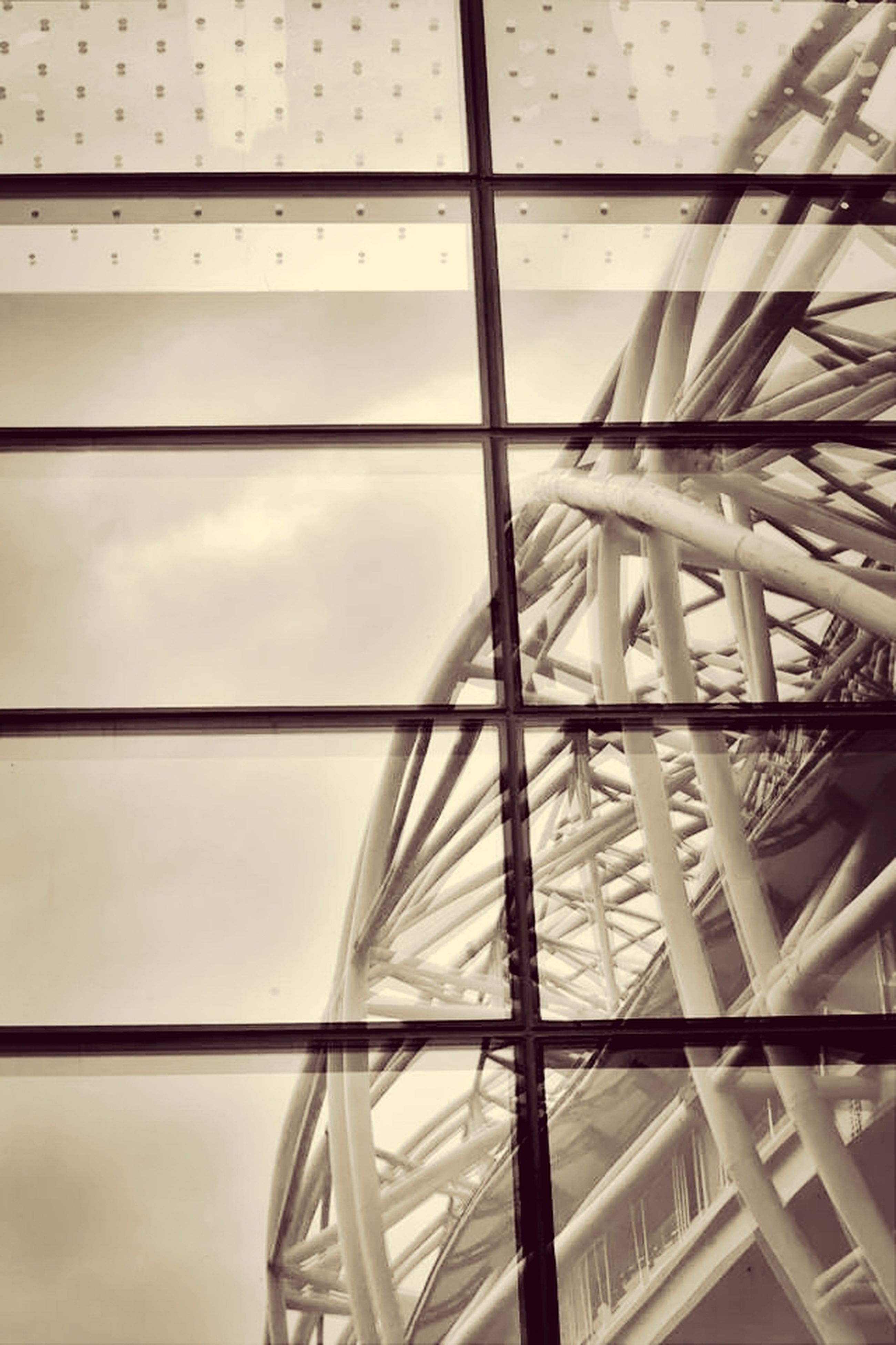 low angle view, built structure, architecture, indoors, glass - material, window, modern, transparent, pattern, metal, building exterior, directly below, day, architectural feature, building, no people, geometric shape, sky, part of, metallic