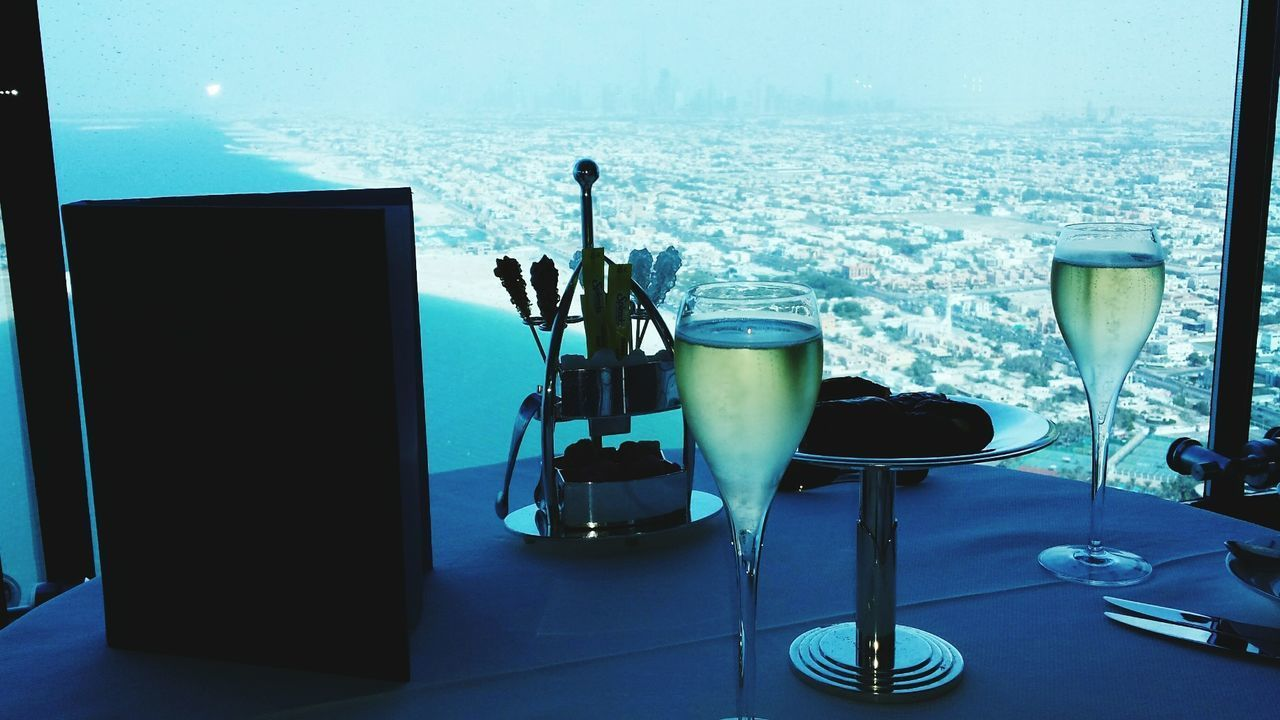 Close-Up Of Champagne In Glasses Served On Table Against Cityscape