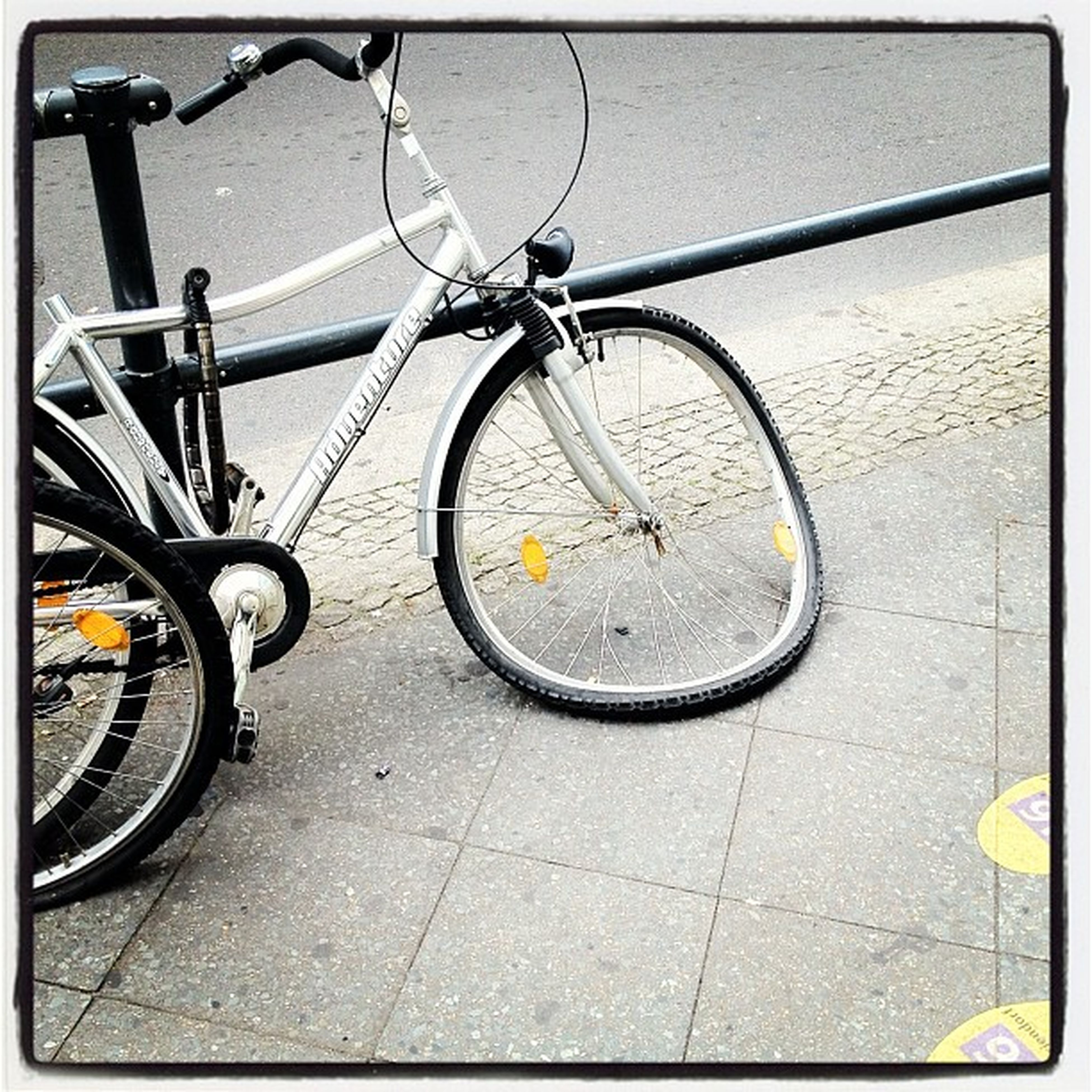 bicycle, transfer print, transportation, mode of transport, auto post production filter, land vehicle, stationary, wheel, parking, street, parked, outdoors, no people, day, sidewalk, wall - building feature, cycle, road, tire, sunlight