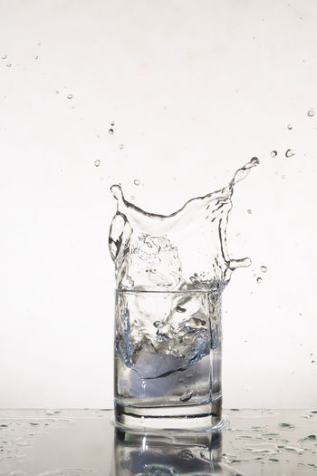 Alcohol Carbonated Close-up Cold Drink Cold Temperature Drink Drinking Glass Drinking Water Drop Freshness Impact Indoors  Motion No People Purified Water Purity Refreshment Spilling Splashing Splattered Studio Shot Water Wet White Background