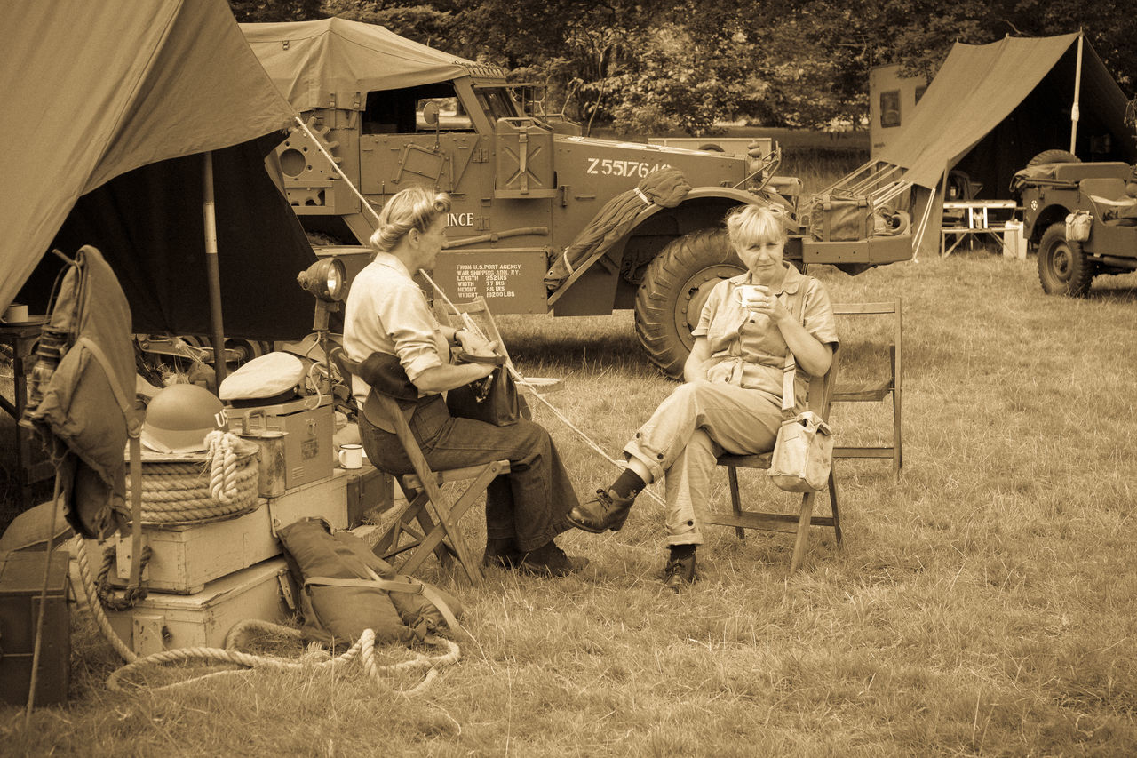 BOCONNOC, LOSTWITHIEL, CORNWALL, ENGLAND, UK - JULY 30, 2016- Women In American World War Two Costume or Dress Sitting Drinking in Army Camp Re-enactment. Sepia and Grain Effect added for Intentional Vintage Filter. Editorial Use Only. American Bivouac Costume Dress Editorial  Female Grain Effect Heritage Historic History Ladies Memorabilia Monochrome People Period Reenactment Retro Tent Vintage War Women World War 2 World War Two WWII Camp First Eyeem Photo
