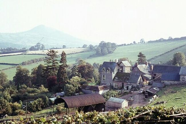 Wales UK Walking In The Hills Brecon Beacons Welsh Farm Skirrid Fawr Mountain Late Summer Afternoon Sunshine Farmhouse when I was a student Fields Trees Hillside Hills Summer Vacation Old Film Photo Mist Distance