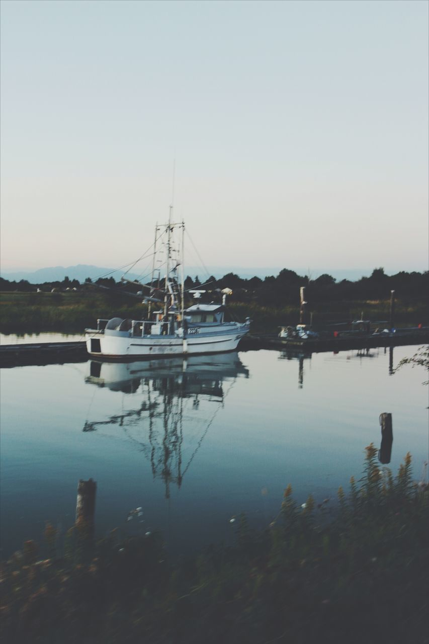 water, reflection, nautical vessel, outdoors, nature, no people, moored, tranquility, lake, transportation, clear sky, harbor, scenics, built structure, sailboat, day, sky, mountain, building exterior, beauty in nature, architecture